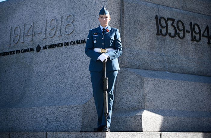 slide - A person in a blue military uniform stands at the top of granite stairs in front of granite walls with her hands resting on the butt of a rifle that is upside down in front of her.