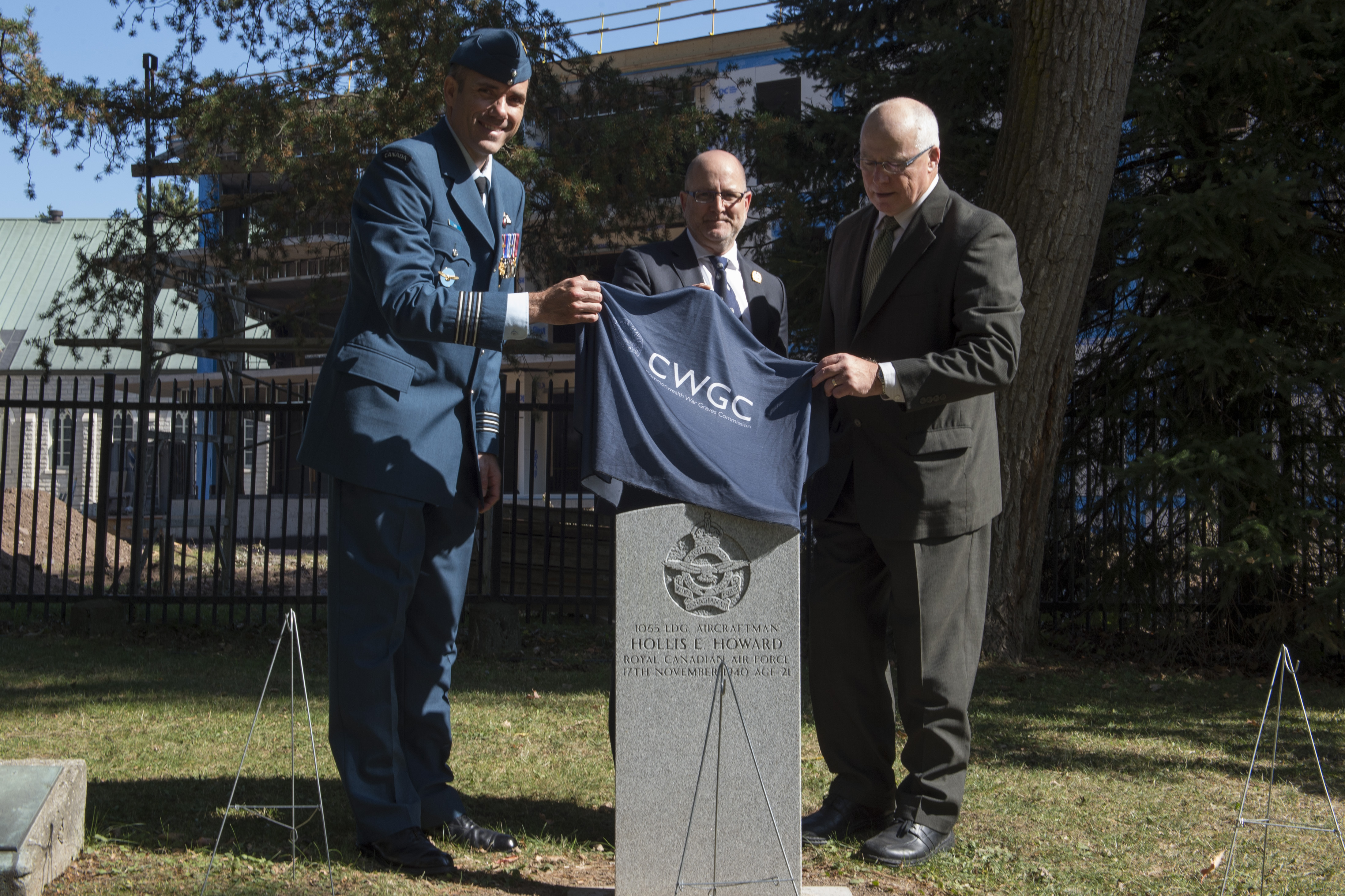 A man dressed in a blue Air Force uniform and two other men in civilian suits remove a piece of cloth covering a grave marker.