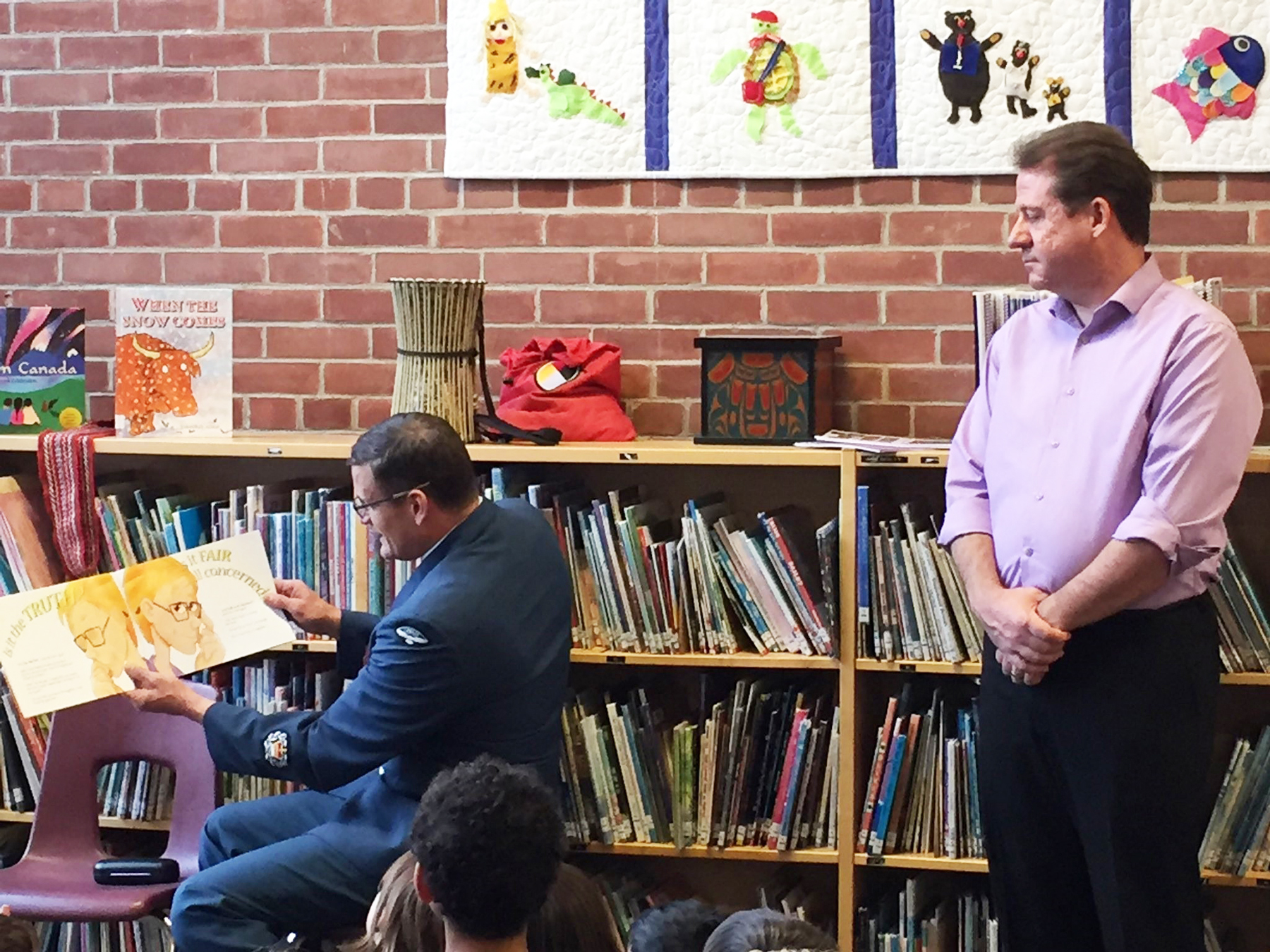 On November 15, 2017, Master Warrant Officer Jason Houle of 16 Wing Borden reads Andy & Elmer's Apple Dumpling Adventure to Grade Two students (and Rotarian Ian Pavlik) at Oakley Park Public School in Barrie, Ontario. PHOTO: Heidi Cameron-Armstrong, Oakley Park Principal.
