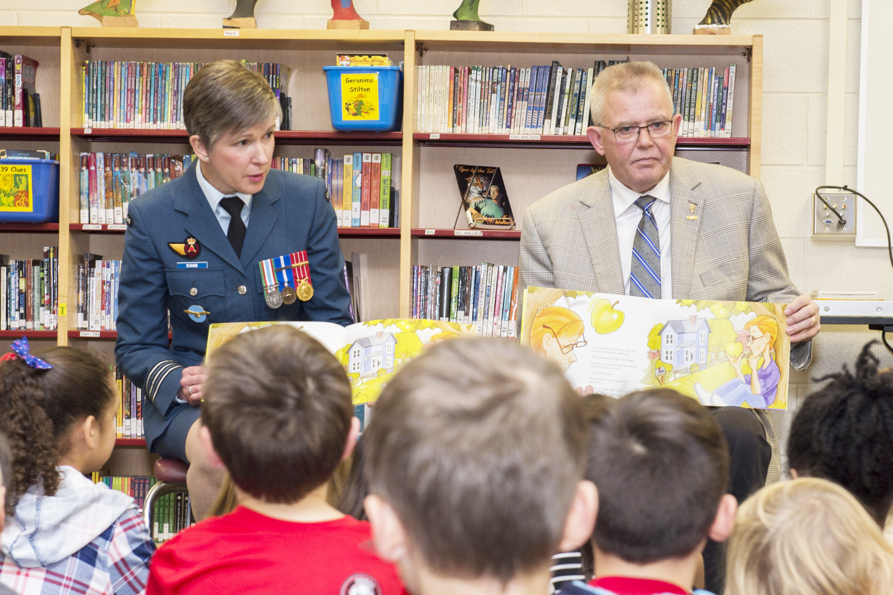 A woman in a blue uniform with medals and a man in a beige suit, both facing the camera, sit in a classroom and read to a group of young children who are sitting with their backs to the camera.