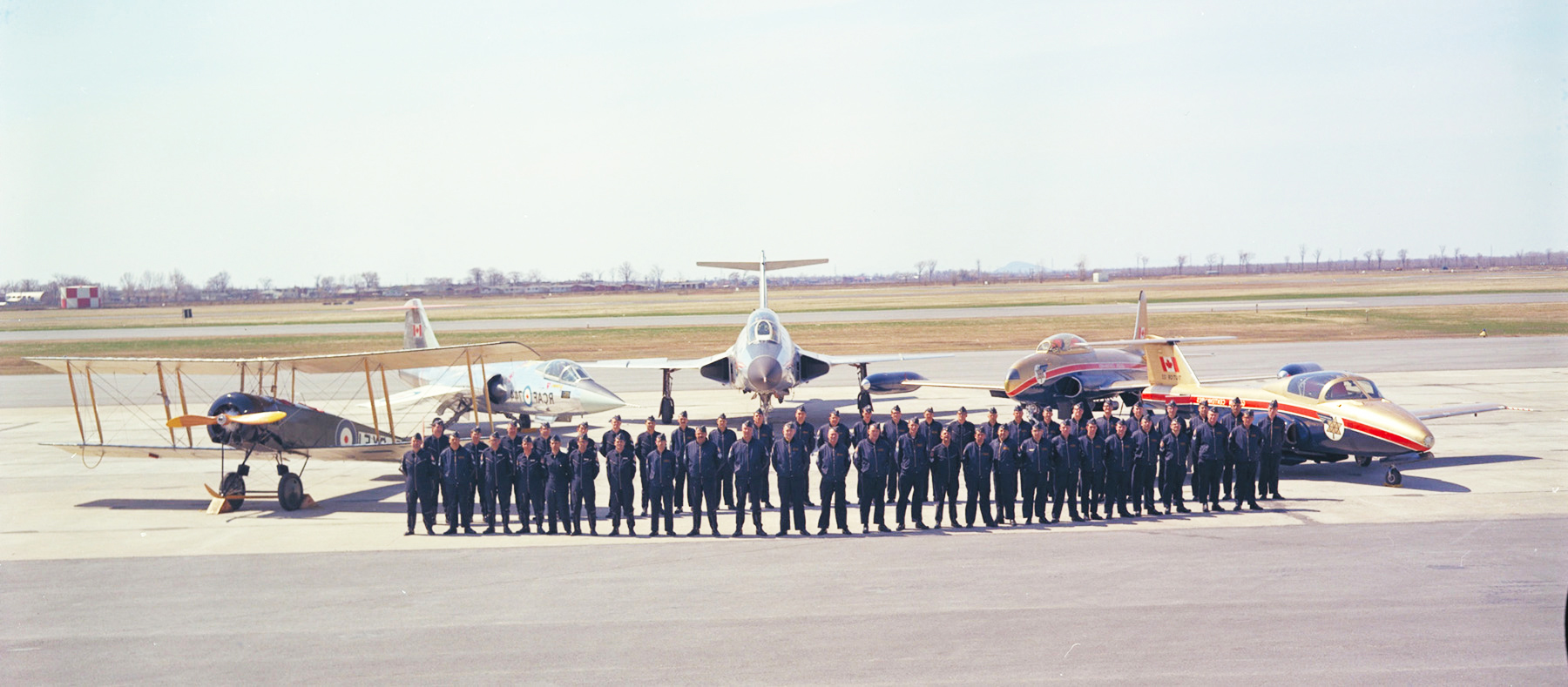 1967 Canadian Armed Forces Golden Centennaires aircrew and groundcrew gather for a photograph in front of five of the team's show aircraft: from left, an Avro 504K biplane, a CF-104 Starfighter, a CF-101 Voodoo, a CT-133 Silver Star, and a CT-114 Tutor (the primary Centennaire aircraft). PHOTO: DND Archives, REC67-479