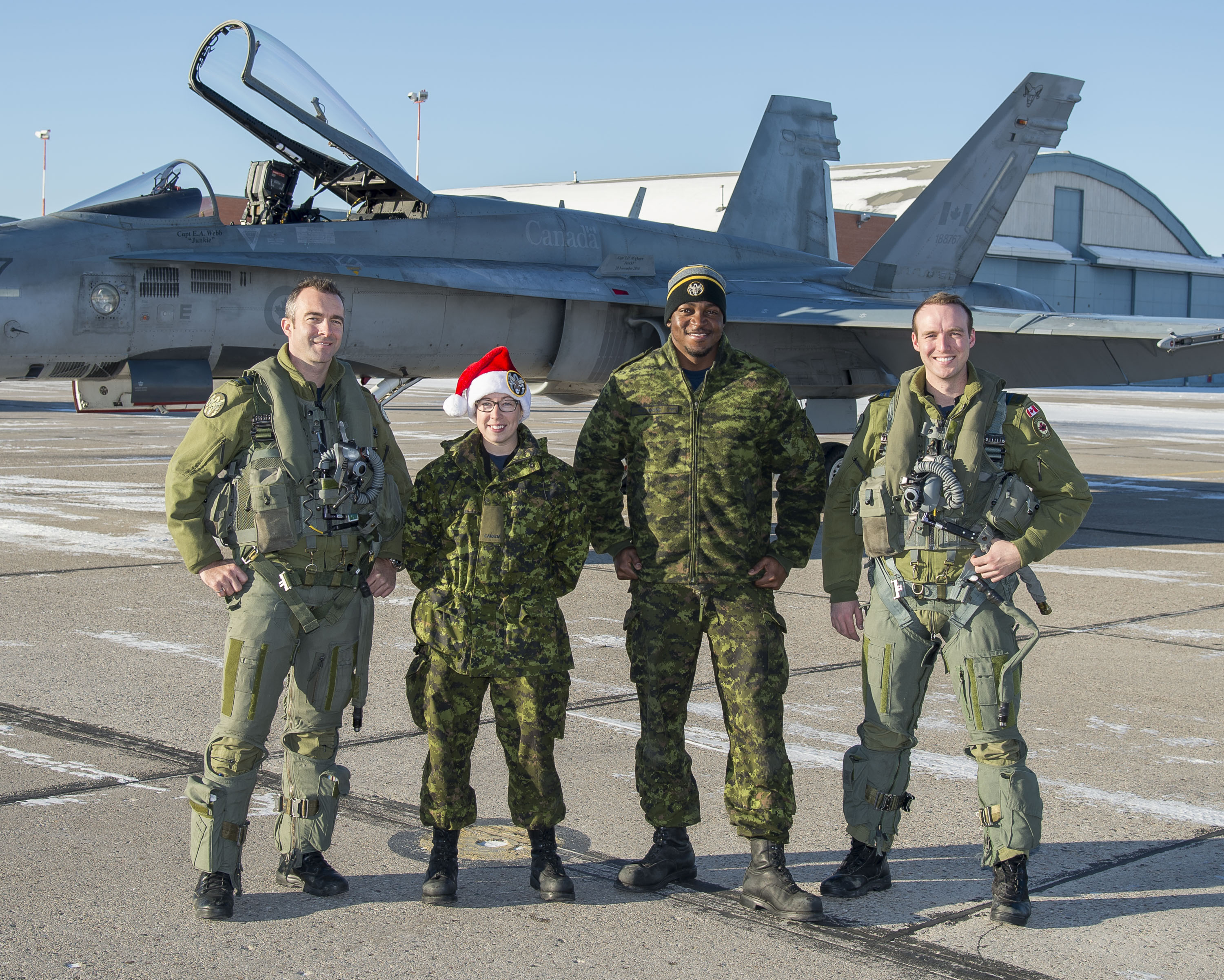 Two people wearing olive green flying suits and two wearing disruptive pattern green military uniforms, one wearing a red Santa Claus hat, stand outdoors in front of a gray fighter jet.