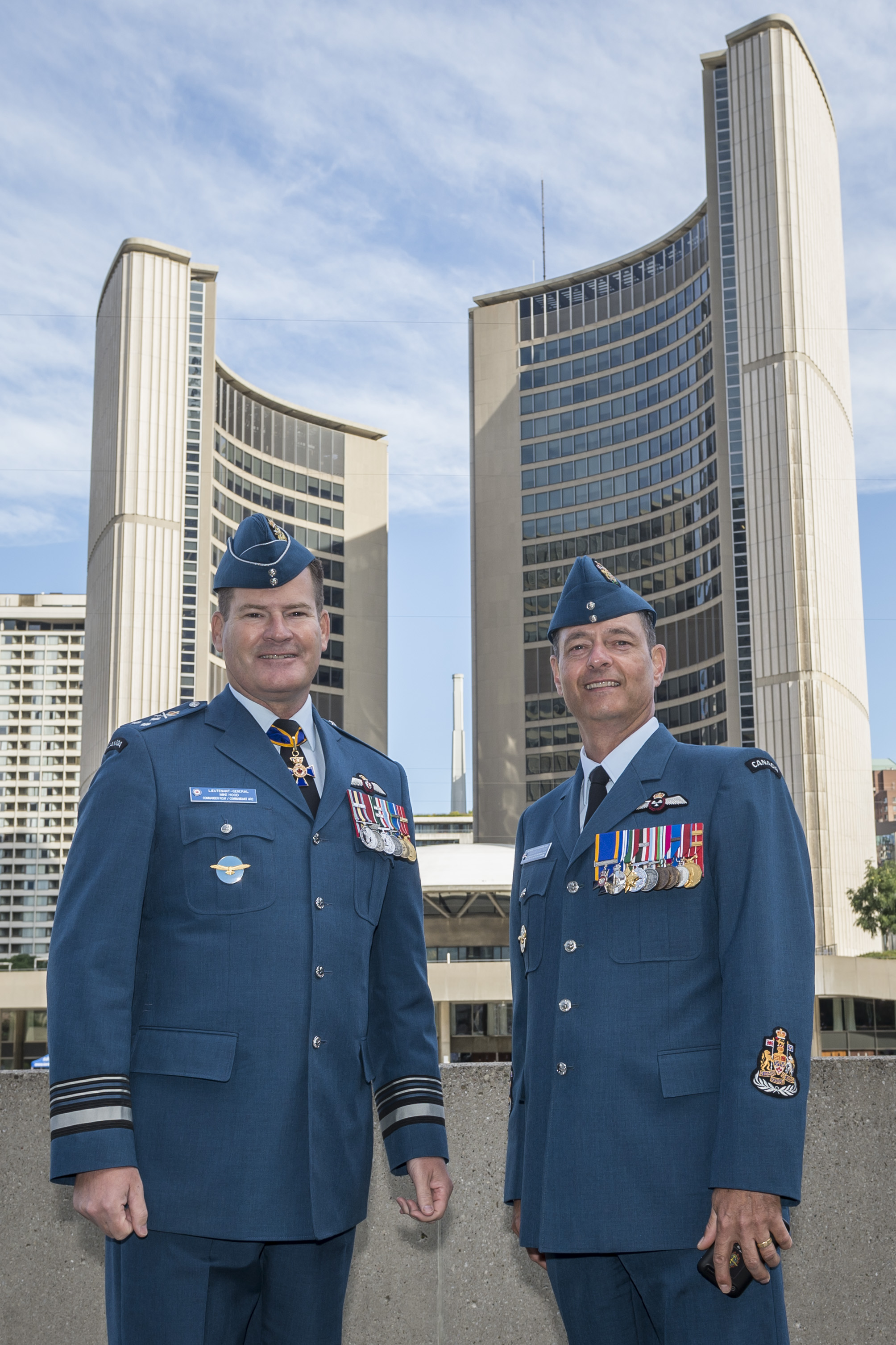 Two men wearing blue military tunics and hats stand in front of two curved tall buildings (the Toronto City Hall).