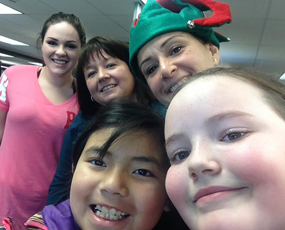 Two girls and three women, one wearing an elf hat, take a selfie.