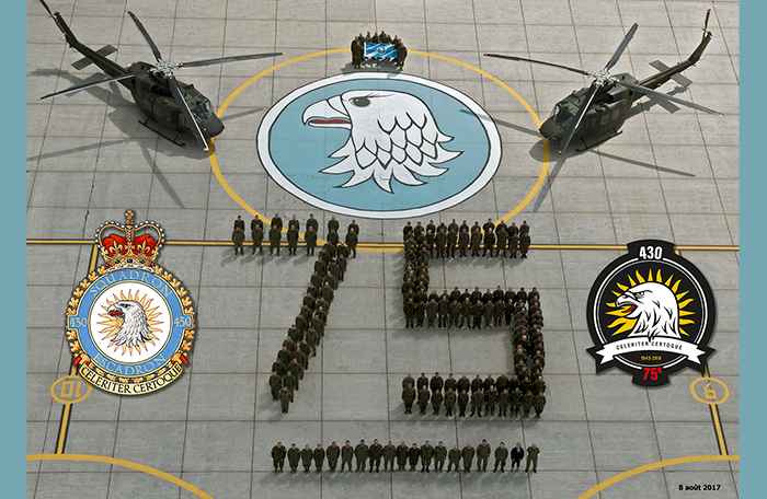 "slide - People in green or disruptive pattern uniforms stand on tarmac so as to spell out ""75"". Behind are two helicopters, 13 people holding a blue and white flag, and a blue and white gyrfalcon's head badge."