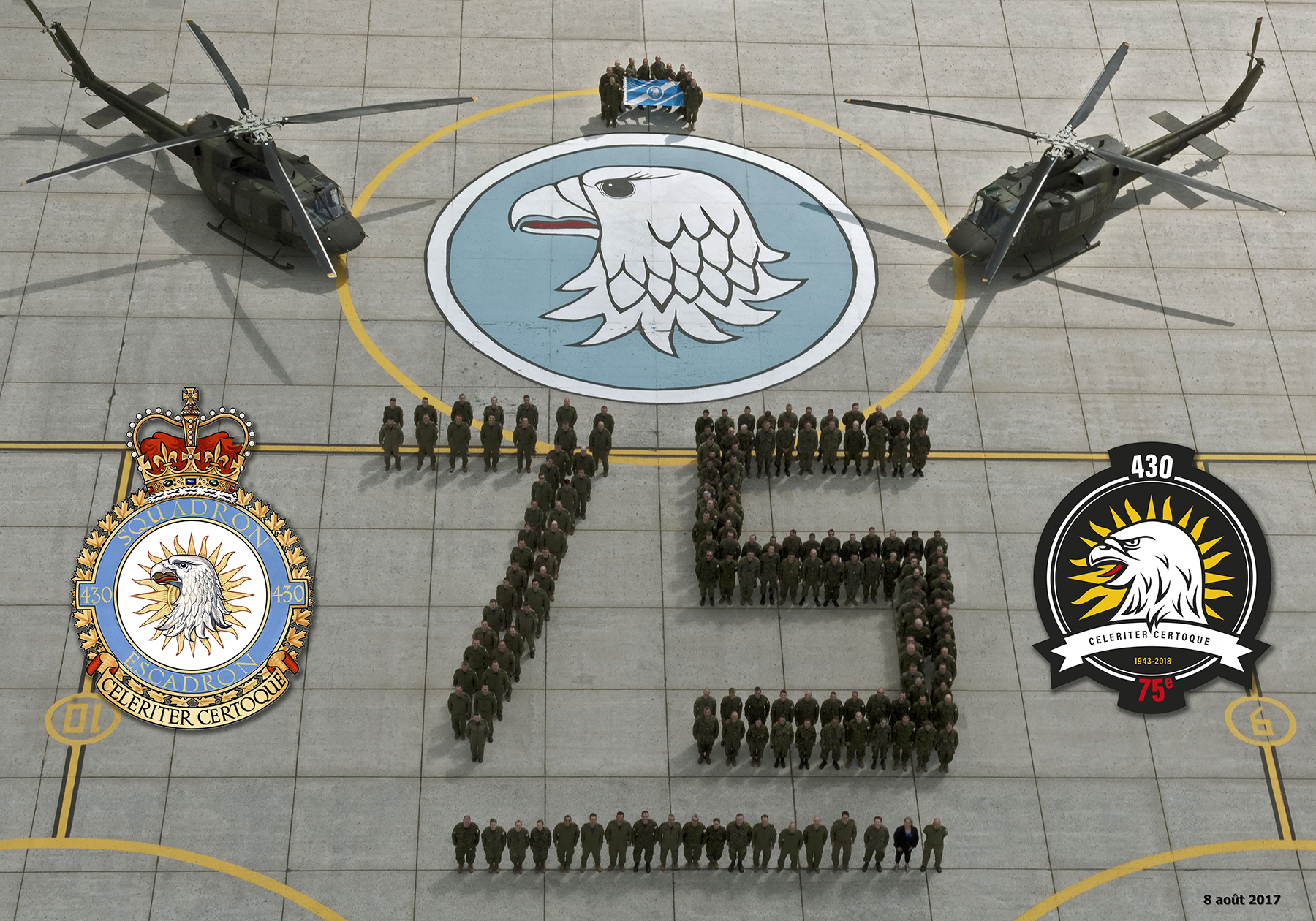 "People in green or disruptive pattern uniforms stand on tarmac so as to spell out ""75"". Behind are two helicopters, 13 people holding a blue and white flag, and a blue and white gyrfalcon's head badge."