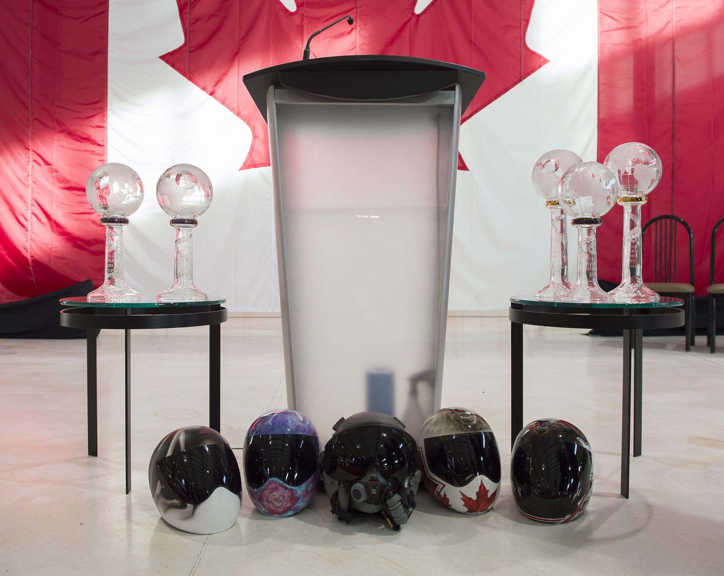 An RCAF CF-18 pilot's helmet rests among the athlete's helmets in front of the speaker's podium during the Bobsleigh Canada Skeleton nominated athletes ceremony at Signature Flight Support, Calgary, Alberta, on January 24, 2018. PHOTO: Ordinary Seaman Justin Spinello, CK03-2018-0012-003