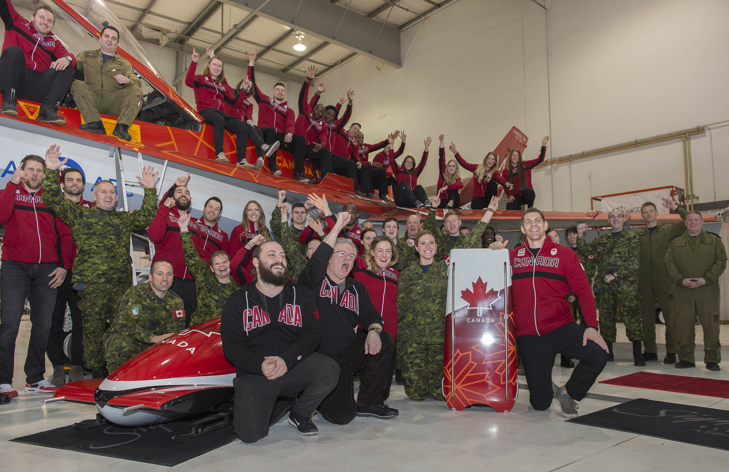 Royal Canadian Air Force personnel, 2018 Olympic Winter Games nominated athletes, the designer of the Olympic bobsleigh and skeleton sleds Josh Dornan (front left), and the designer of the Canada 150 CF-18 Demonstration Hornet Jim Belliveau (front, second from the left) pose for a group photo with the Demonstration Hornet and the newly-revealed bobsleigh and skeleton sleds inspired by the Demo Hornet. The reveal took place as part of a ceremony at the Signature Flight Support, Calgary, Alberta on January 24, 2018, during which Bobsleigh Canada Skeleton announced the nominated athletes and coaches to Canada's Olympic bobsleigh and skeleton teams for the 2018 Olympic Winter Games in PyeongChang, South Korea. PHOTO: Ordinary Seaman Justin Spinello, CK03-2018-0012-006