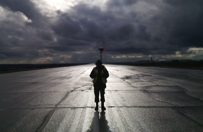 slide - A person wearing a reflective vest and standing in moonlight on a runway holds a tall stick with something mushroom-shaped, with small reflective flags, on top.