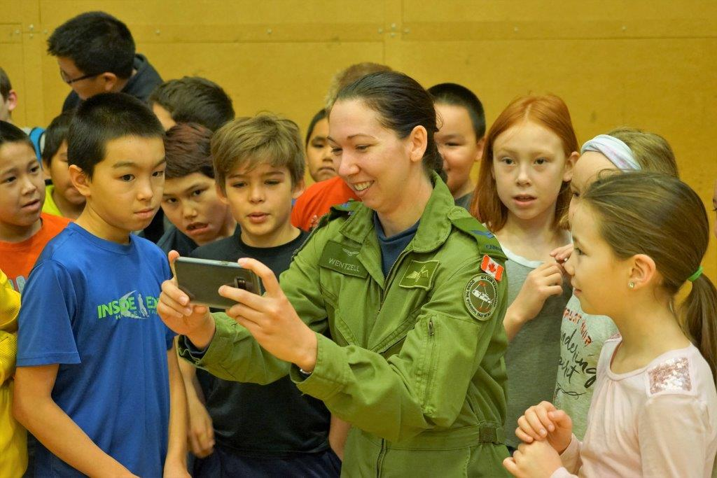Corporal Kayla Wentzell shares photos with students at Joamie School in Iqaluit, Nunavut, during a visit to the school by the members of an Aurora crew from 405 Long Range Patrol Squadron, located at 14 Wing Greenwood, Nova Scotia. PHOTO: Major Jeff Robert