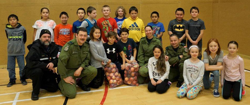 (From left) Petty Officer First Class Jay Logan of Joint Task Force North Detachment Nunavut, and Captain Joseph MacKinnon, Corporal Kayla Wentzell and Captain Colin Clansey of 405 Long Range Patrol Squadron pause for a photo with students at Joamie School in Iqualuit, Nunavut. The 405 Squadron Aurora crew brought the apples from the Annapolis Valley in Nova Scotia; they were added to the school's daily breakfast program after the crew visited the school for morning assembly. PHOTO: Major Jeff Robert, Detachment Commander, Joint Task Force North Detachment Nunavut
