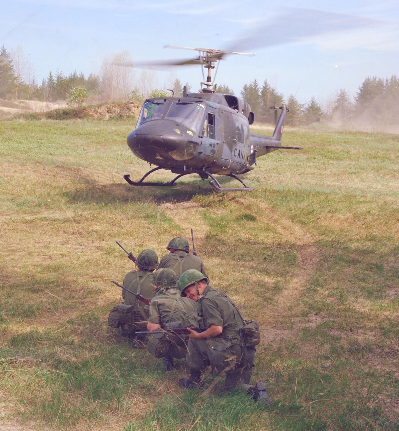 Four soldiers wait for an airlift by a CH-135 Twin Huey helicopter during a training event supported by 427 Squadron around 1982. An important part of 427 Squadron's celebrated history of aviation excellence, the CH-135 Twin Huey helicopter served Army bases across Canada and was frequently used on United Nations missions around the world. 427 Squadron retired the CH-135 Twin Huey in 1997, after receiving the last of the newly-purchased Bell CH-146 Griffon fleet.  PHOTO: DND Archives, ISC82-977