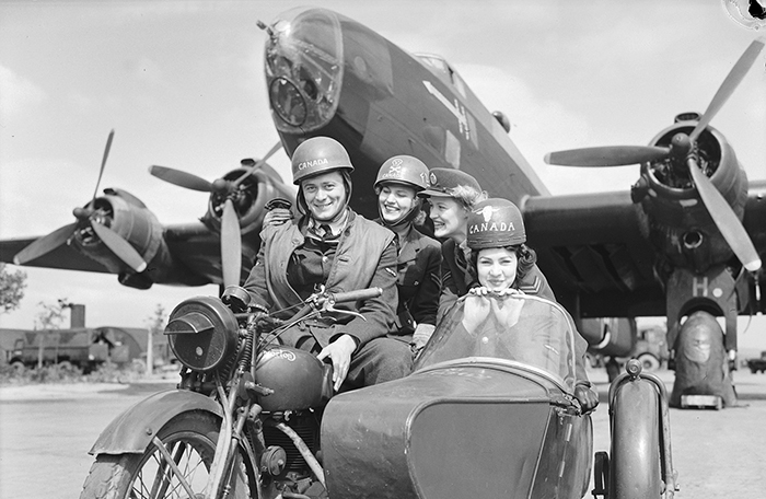 slide - In a vintage black and white photo, four people in military uniforms are seated on a motorcycle or in its sidecar in front of a large aircraft.