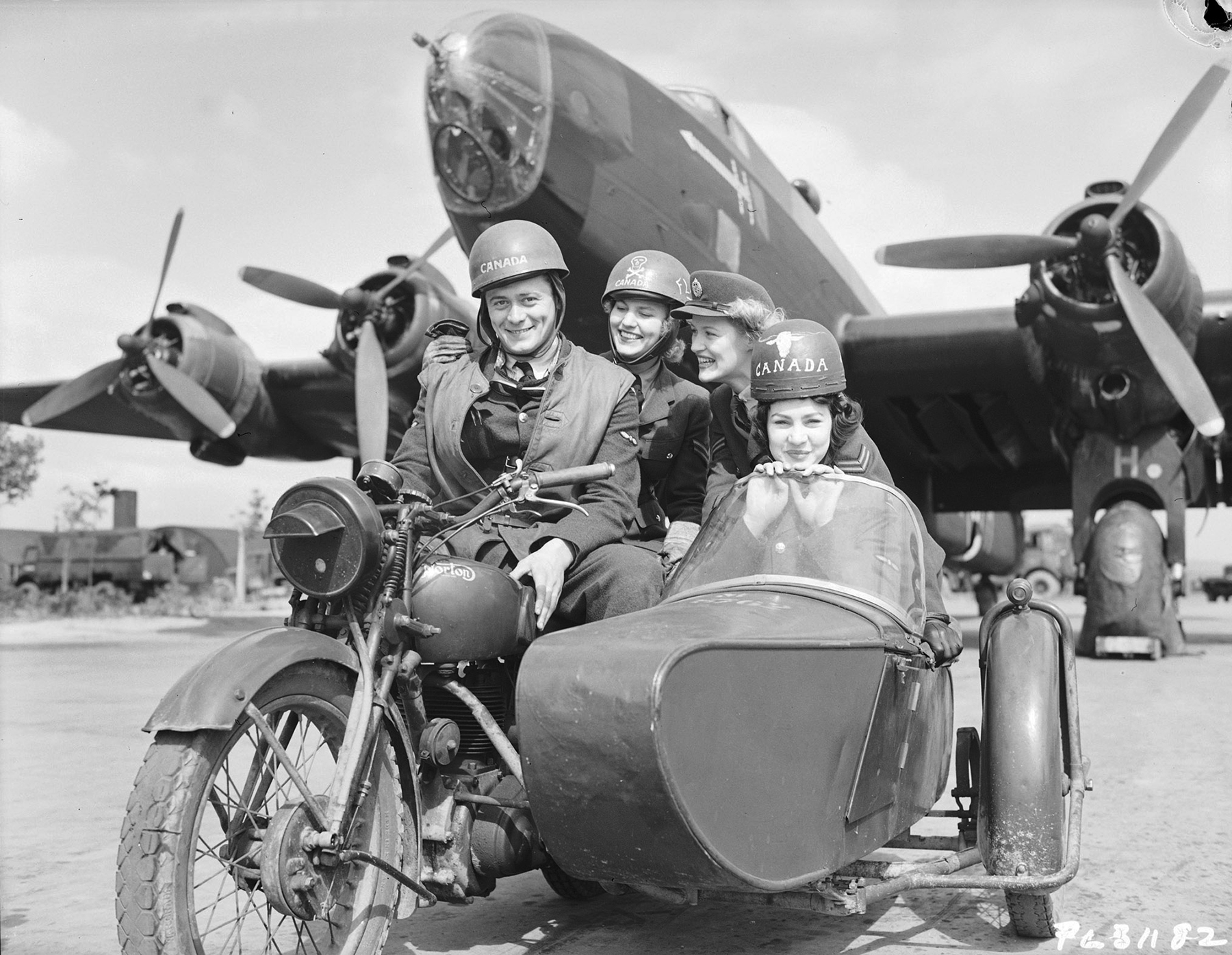 In a vintage black and white photo, four people in military uniforms are seated on a motorcycle or in its sidecar in front of a large aircraft.