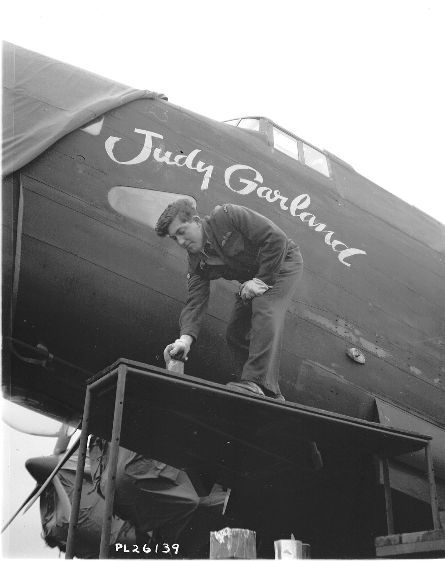 "On November 16, 1943, Flight Sergeant J. Mawson of Kingston, Ontario paints a design displaying the name of film star Judy Garland on a 427 Squadron aircraft. On May 24, 1943, American film giant Metro-Goldwyn-Mayer (MGM) had adopted 427 Squadron and allowed the names of such stars as Judy Garland, Lana Turner and Joan Crawford to be displayed on the squadron's aircraft. As legend has it, MGM provided all 427 Squadron ""Lions: with a lifetime pass to its theaters across North America. In addition, MGM presented a bronze lion to the squadron. This gift and the affiliation with the MGM lion mascot strengthened the squadron's Lion nickname. PHOTO: DND Archives, PL-26139"