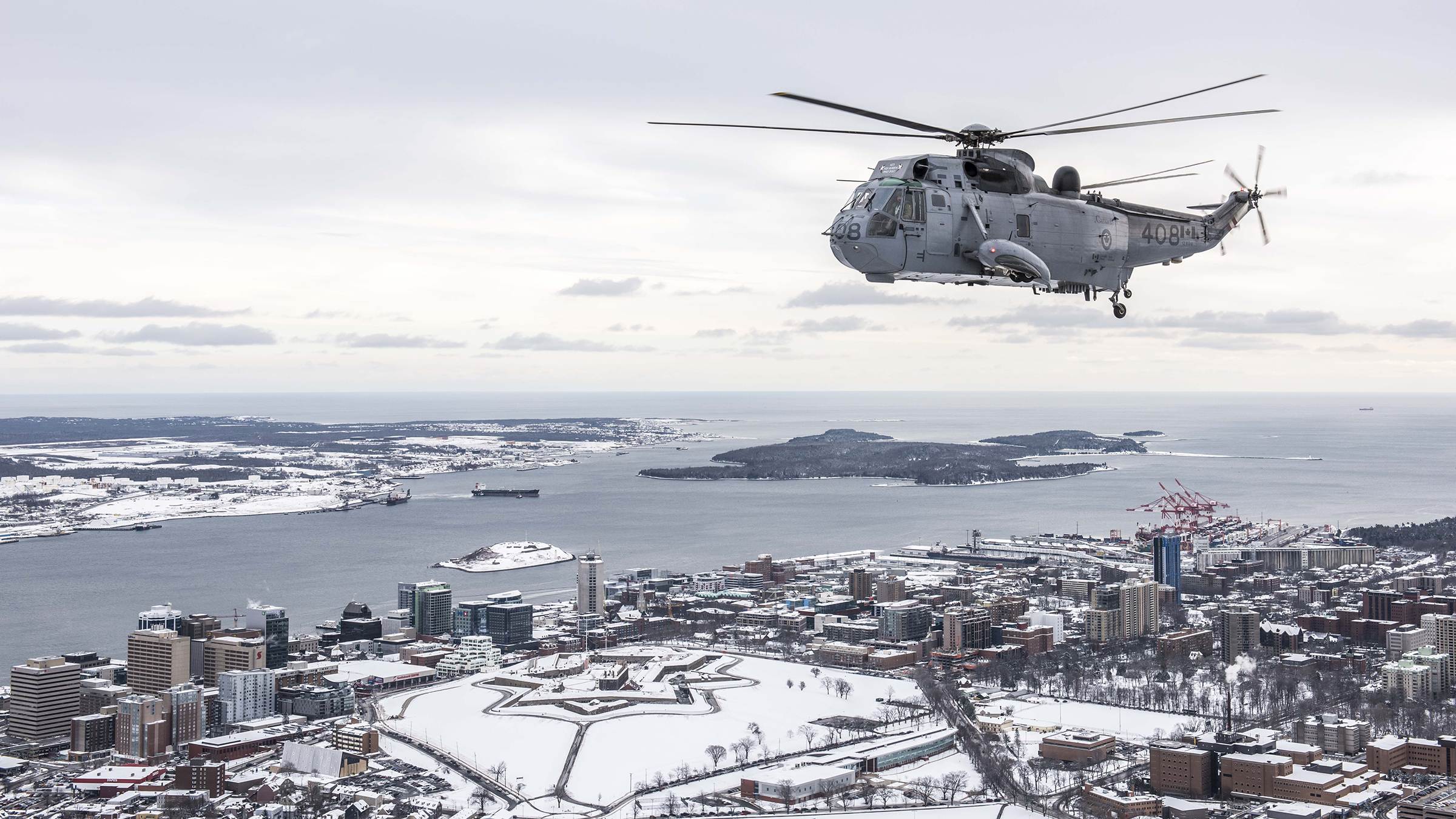 A CH-124 Sea King helicopter from 423 Maritime Helicopter Squadron, based at Shearwater, Nova Scotia, flies over Halifax on January 19, 2018. The squadron conducted its final Sea King flight on January 26, 2018, and will now turn its full attention to transitioning to the RCAF's new maritime helicopter, the CH-148 Cyclone. Sea King operations on the east and west coasts will be conducted by 443 Maritime Helicopter Squadron, located in British Columbia, until the helicopter retires at the end of 2018. PHOTO: Corporal Anthony Laviolette, SW04-2018-0020-015