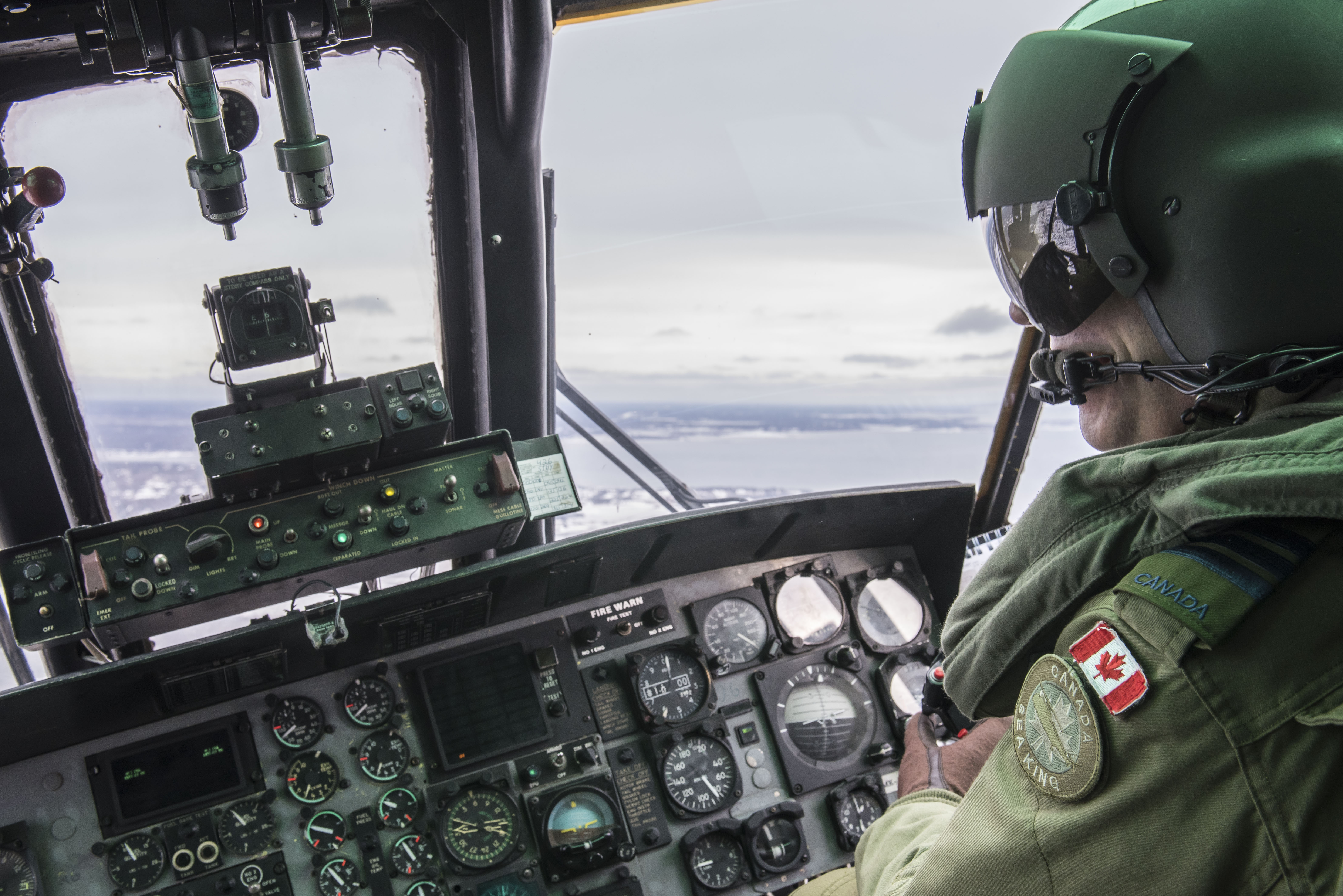 Lieutenant-Colonel Jody Smith, commanding officer of 423 Maritime Helicopter Squadron, flies a CH-124 Sea King helicopter near Halifax Harbour in Nova Scotia, on January 19, 2018, in preparation for the squadron's final Sea King flight on January 26. PHOTO: Corporal Anthony Laviolette, SW04-2018-0020-018