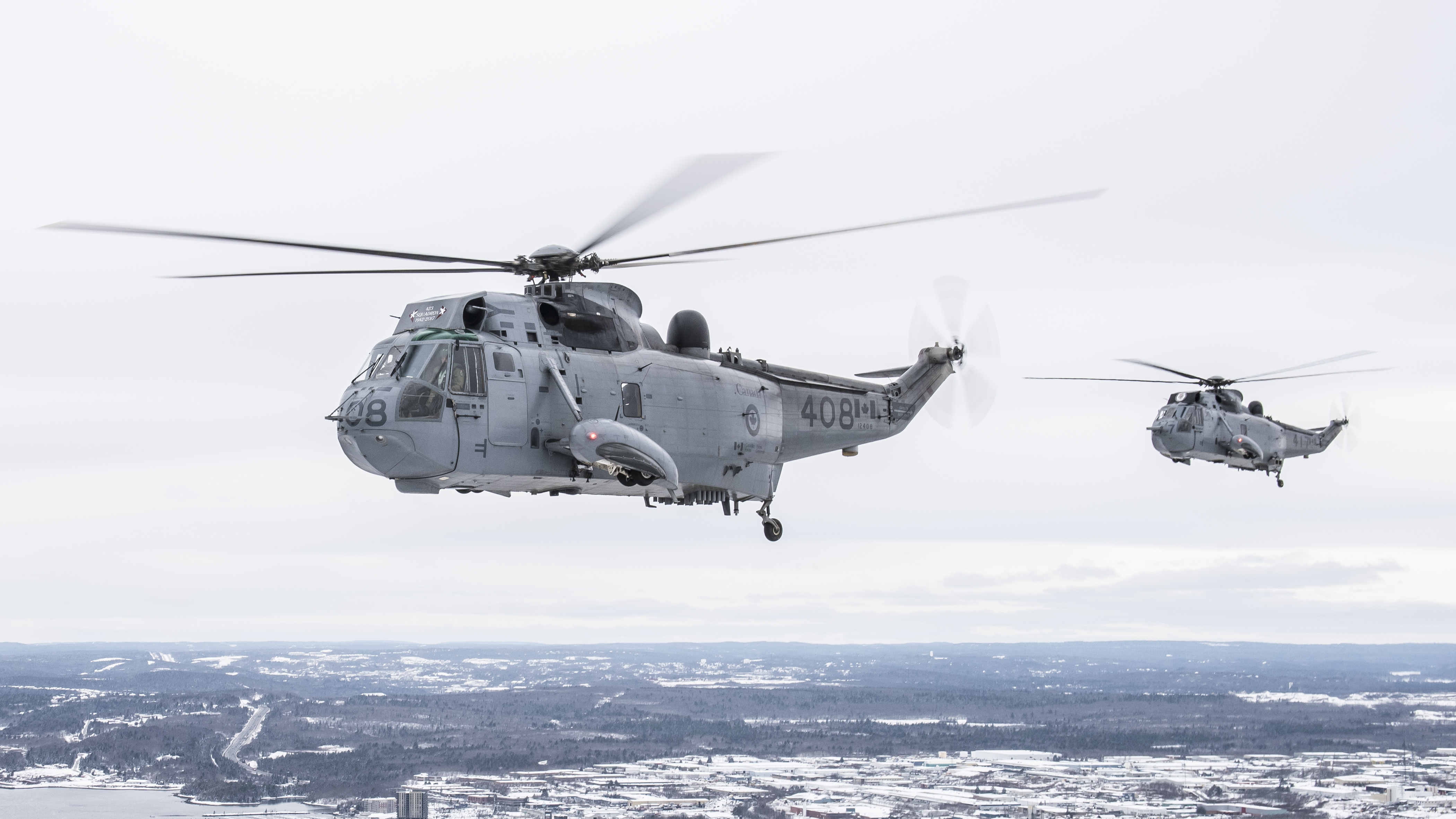 Two Sea King helicopters from 423 Maritime Helicopter Squadron, located at 12 Wing Shearwater, Nova Scotia, fly over the Halifax-Dartmouth area on January 19, 2018, in preparation for the squadron's final Sea King flight on January 26. PHOTO: Corporal Anthony Laviolette, SW04-2018-0020-021