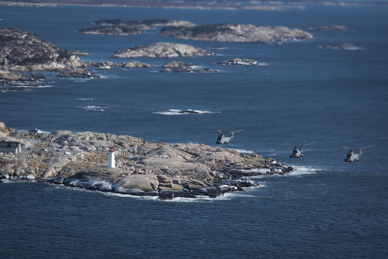 Three Sea King helicopters from 423 Maritime Helicopter Squadron, based at 12 Wing Shearwater, Nova Scotia, fly over Peggy's Cove and its iconic lighthouse on January 26, 2018. It was the squadron's final operational flight with Sea Kings; squadron personnel will now turn their full attention to transitioning to the RCAF's new maritime helicopter, the CH-148 Cyclone. Sea King operations on the east and west coasts will be conducted by 443 Maritime Helicopter Squadron, located in British Columbia, until the Sea King retires at the end of 2018. PHOTO: DND, SW05-2018-0015-003