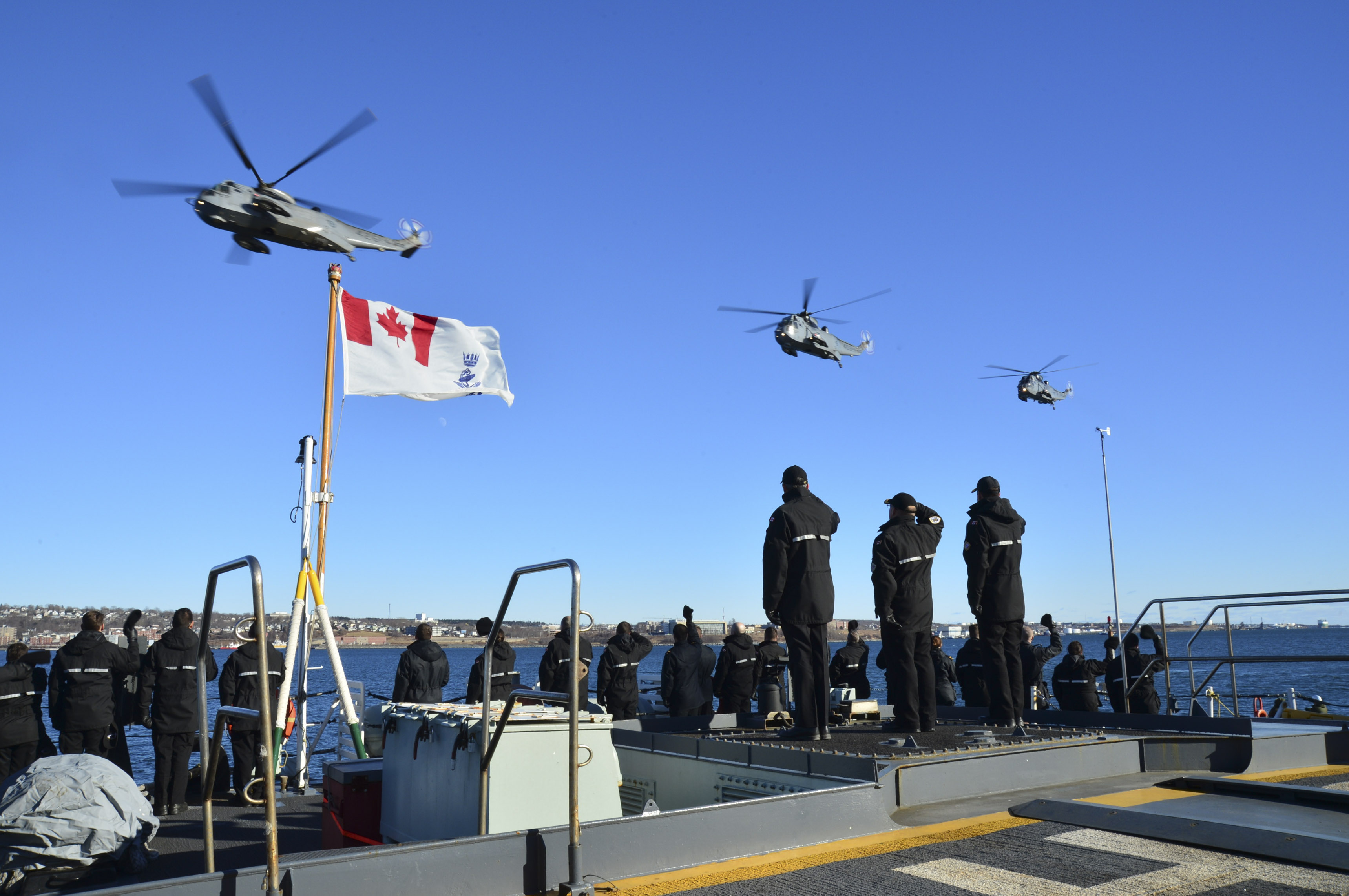 Royal Canadian Navy personnel wave and salute as 423 Maritime Helicopter Squadron conducts its final flight with CH-124 Sea King helicopters over Halifax Harbour on January 26, 2018. The squadron will now focus on transitioning to the CH-148 Cyclone. Sea King operations on the east coast will be carried out by 443 Maritime Helicopter Squadron, which belongs to 12 Wing Shearwater, Nova Scotia, but is based at Patricia Bay, British Columbia, until the Sea Kings retire at the end of 2018. PHOTO: DND