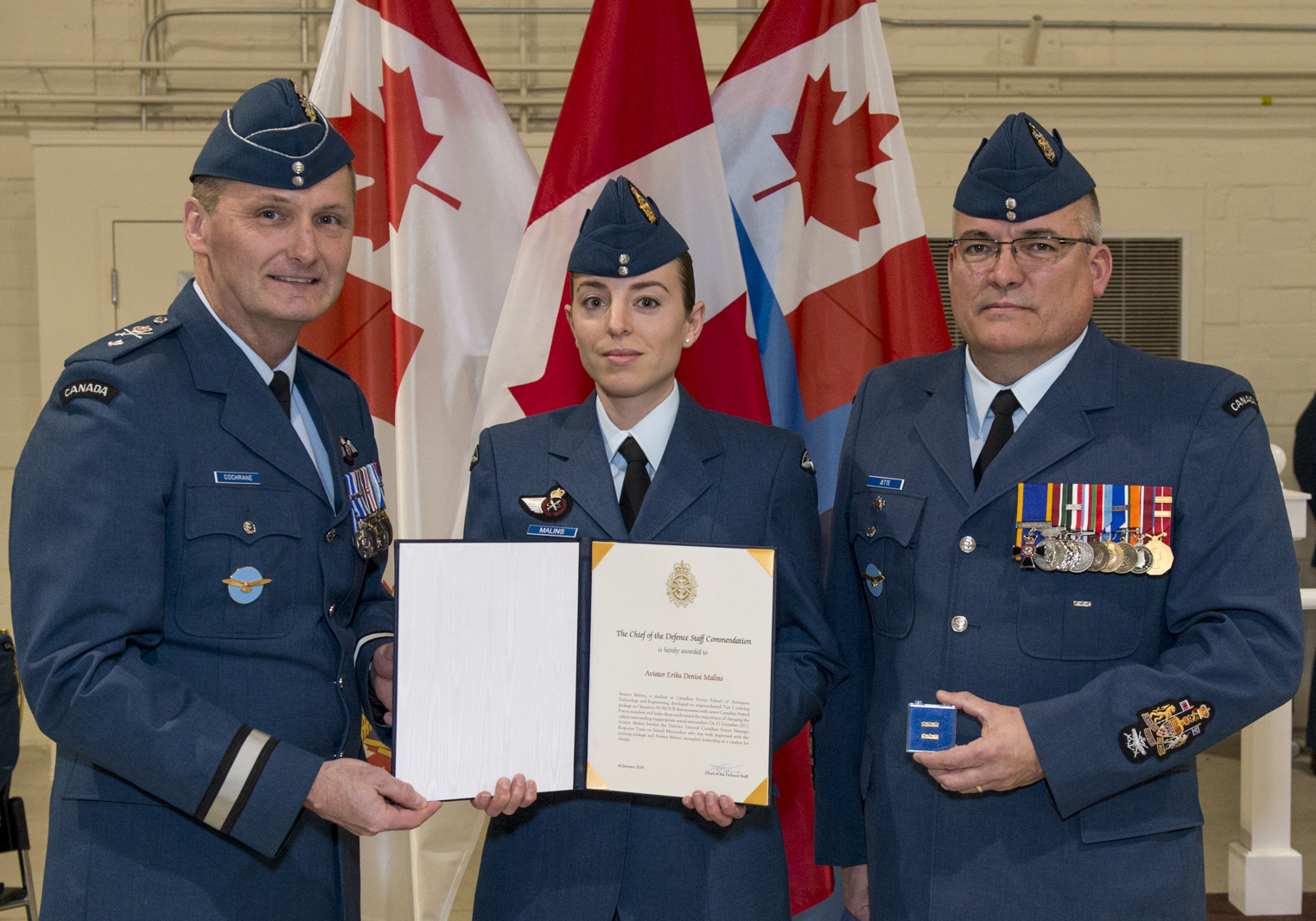 Three people wearing air force uniforms stand beside each other. Two are jointly holding a certificate in a folder.