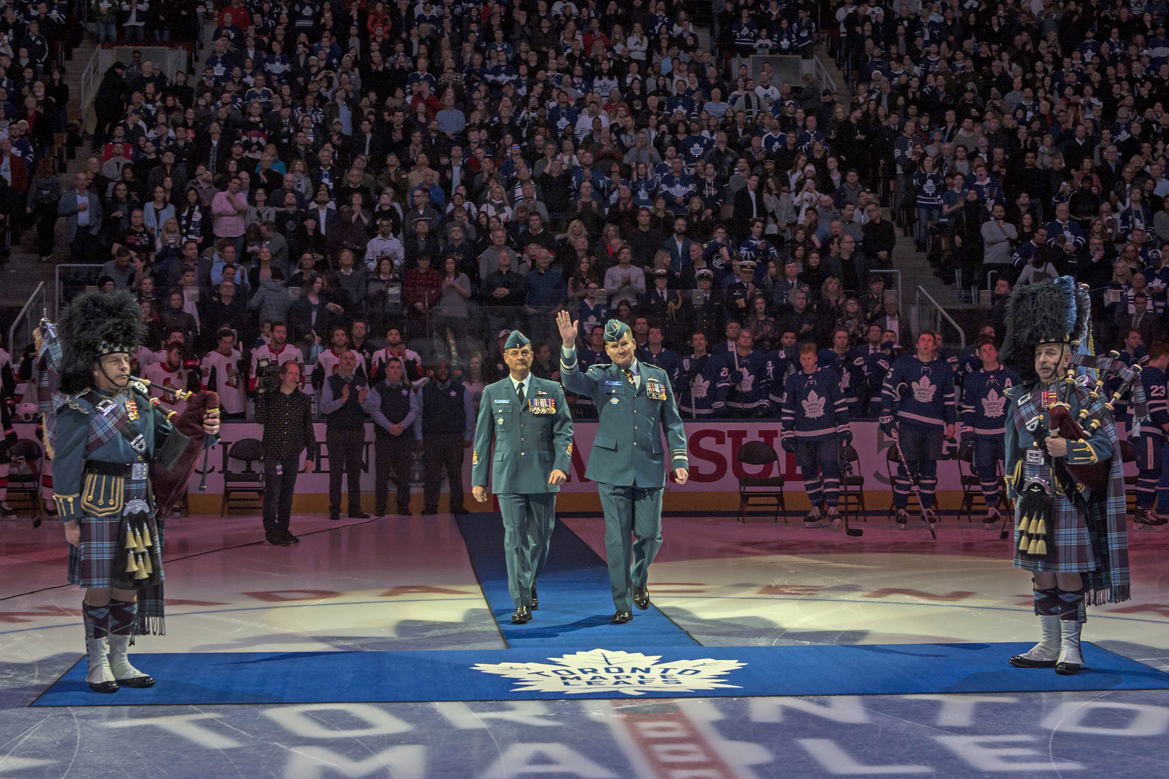 Lieutenant-General Mike Hood, commander of the Royal Canadian Air Force, accompanied by Chief Warrant Officer Gérard Poitras, RCAF command chief warrant officer, waves to the crowd of more than 19,000 at the Air Canada Centre on February 10, 2018, at the beginning of the ceremony transferring the guardianship of the retired RCAF Colours to the Maple Leafs hockey team. PHOTO: Corporal Alana Morin, FA03-2018-0015-001
