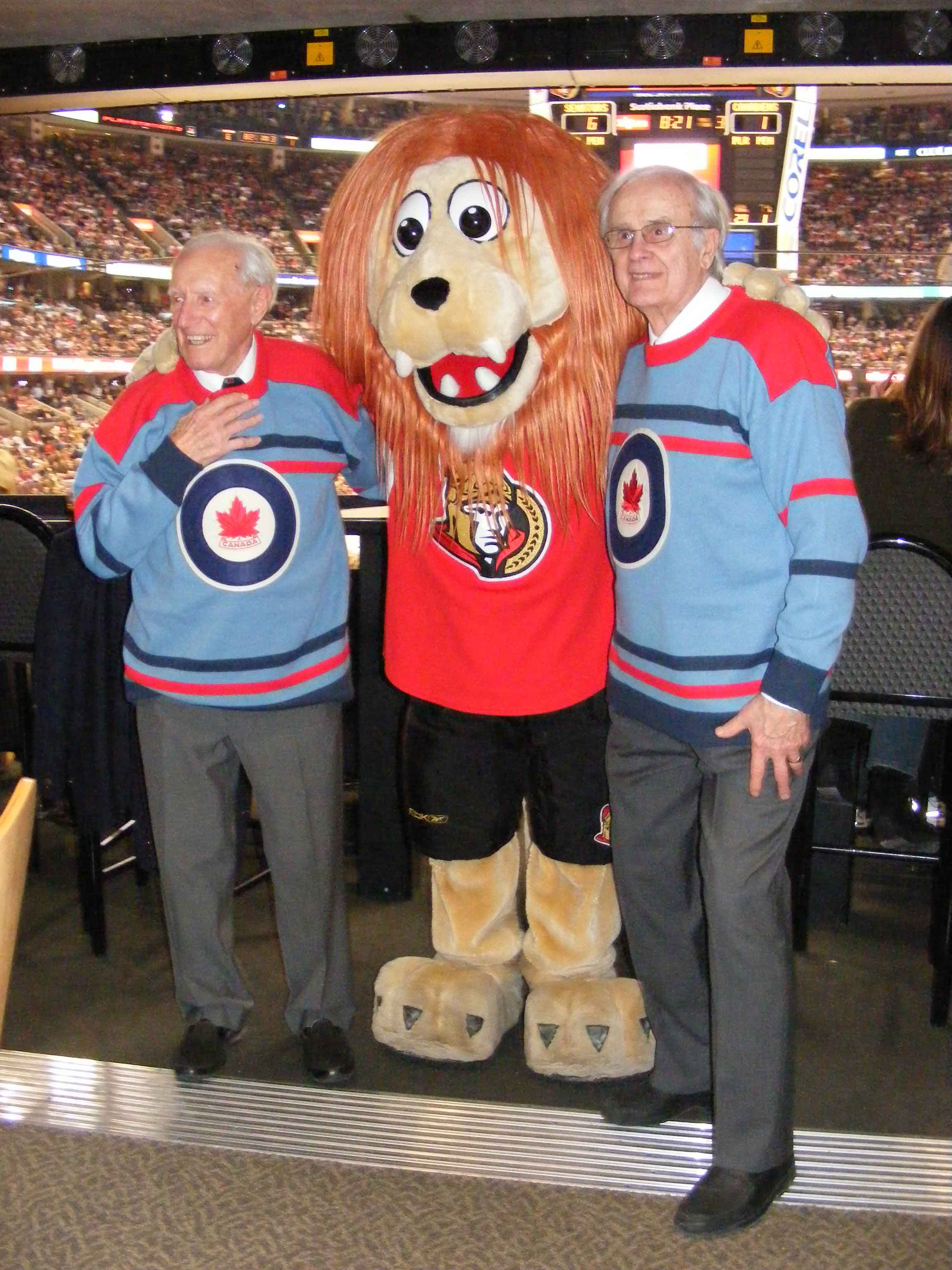 Former RCAF Flyers team mates Ab Renaud (left) and André Laperrière, sporting their replica 1948 Olympics jerseys specially produced by the Royal Canadian Air Force Association, are greeted by Spartacat, the mascot of the Ottawa Senators hockey team. Mr. Renaud and Mr. Laperrière dropped the puck at the February 9, 2008, game between the Senators and the Montreal Canadiens in Ottawa. PHOTO: Dean Black, RCAFA