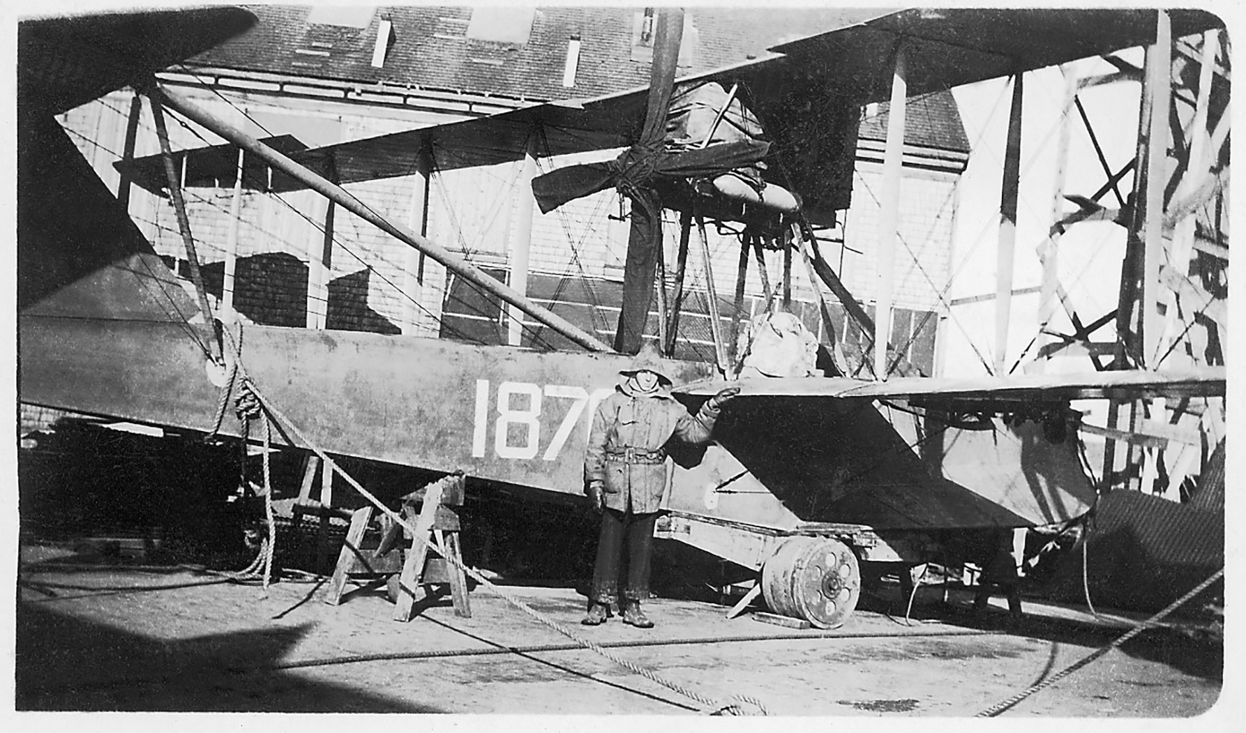 A vintage photo of a person standing beside the fuselage of a large biplane that has its engine mounted on the top wing, with other aircraft and large buildings in the background.