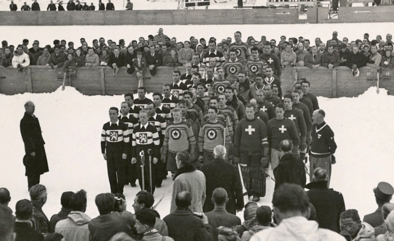 Three hockey teams stand in a close group outdoors with spectators around them.