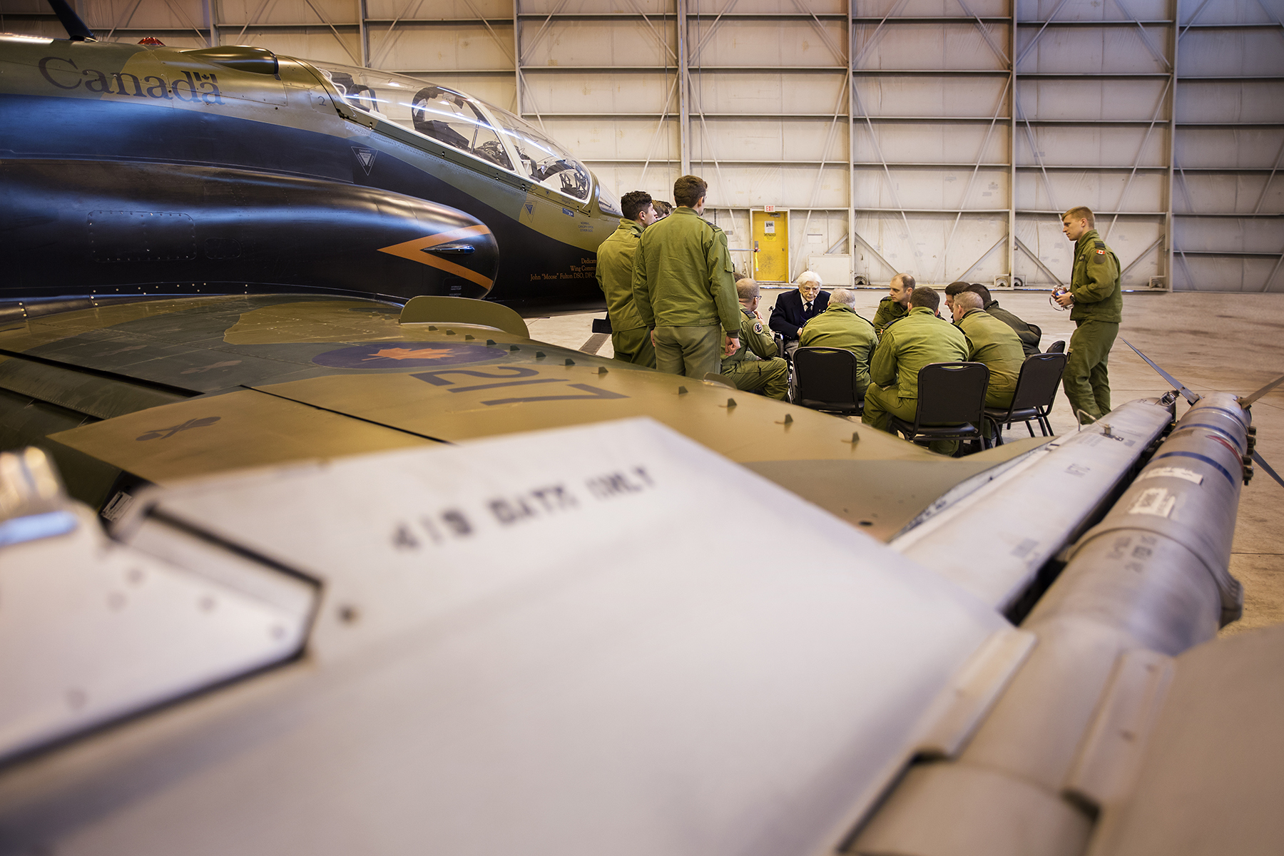 RCAF 419 Tactical Fighter (Training) Squadron members meet with Royal Canadian Air Force Squadron Leader (retired) George Sweanor beside one of their aircraft on February 23, 2018, to talk about the squadron's Second World War service. Squadron Leader Sweanor was a founding member of No. 419 Squadron in 1941. PHOTO: NORAD/USNORTHCOM Public Affairs