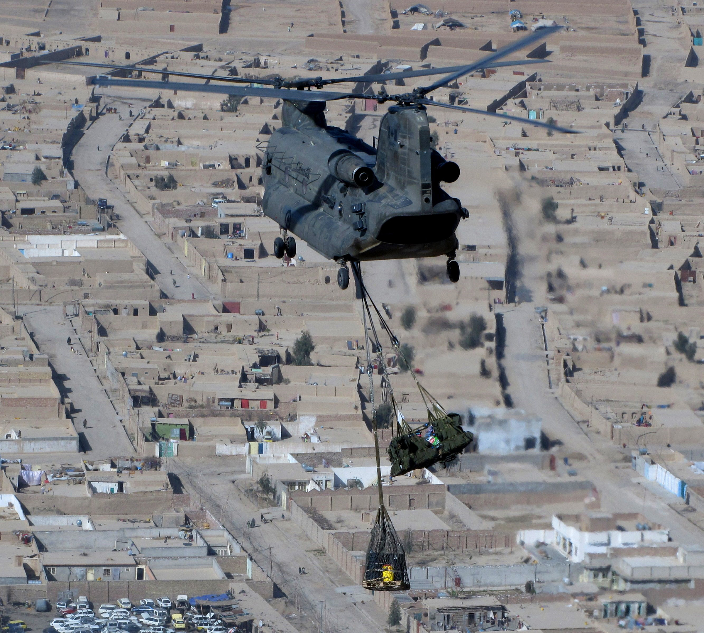 A D-model Chinook helicopter flies over Kandahar City with a slung load. The Chinook slung load capability was used to re-supply forward operating bases. PHOTO: Master Corporal Craig Wiggins, ISX2010-0031