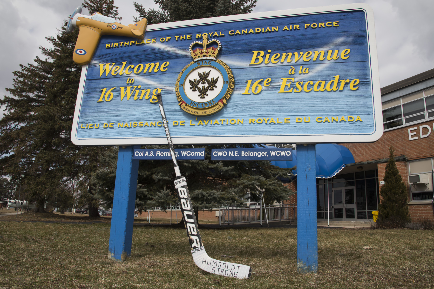 A large outdoor sign with a goalie's hockey stick leaning against it.
