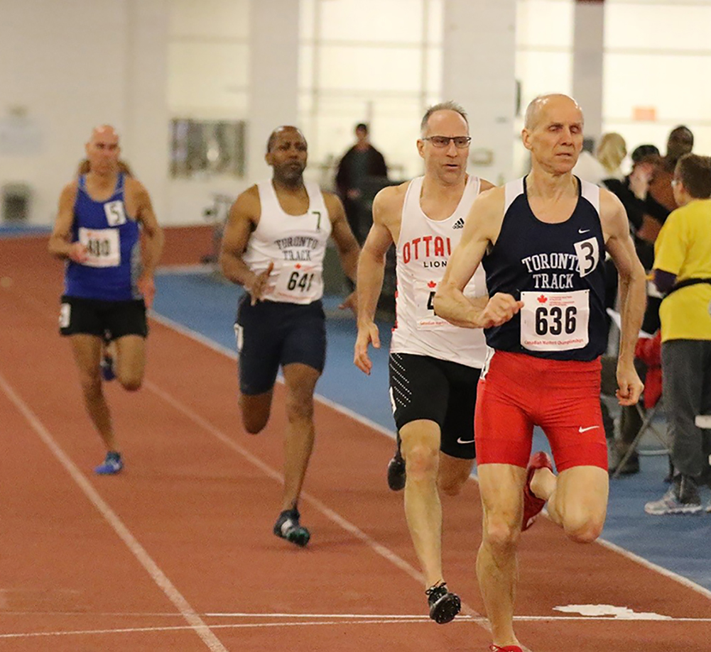 "Major Serge Faucher (""Ottawa Lions"" singlet) and Master Warrant Officer Claude Faucher (blue singlet) race in the 400m at the Canadian Masters Indoor Championships in Toronto, Ontario, on March 11, 2018. PHOTO: John MacMillan"