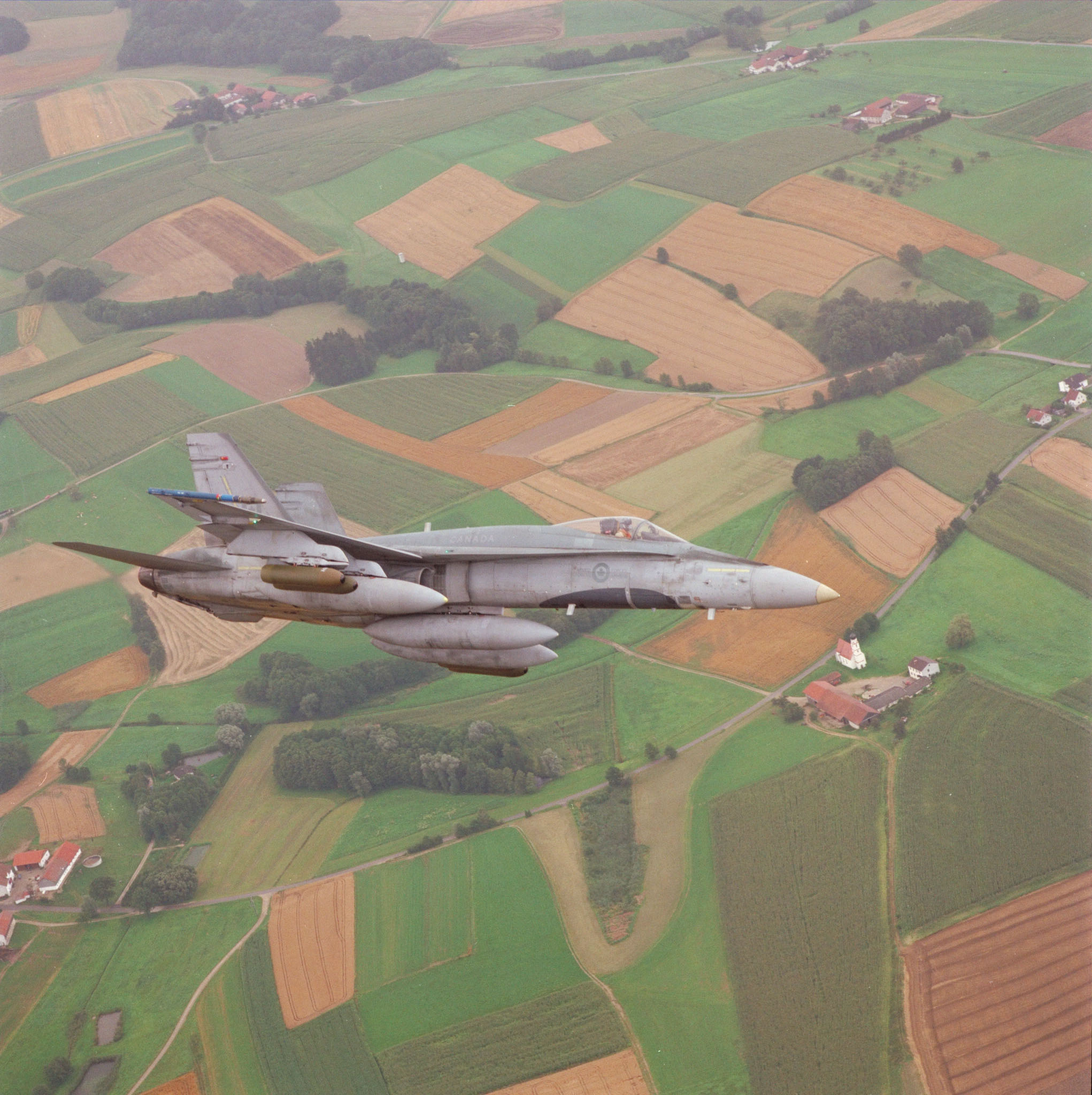 Flown by Captain Doug Stroud, a CF-188 fighter from 409 Tactical Fighter Squadron, located at Canadian Forces Base Baden, flies over Bavarian farmlands in Southern Germany. This photo probably dates from 1987. PHOTO: DND Archives, ISC87-489