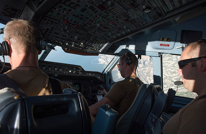 slide - In a cockpit, three men in khaki t-shirts fly an aircraft over a sea port.