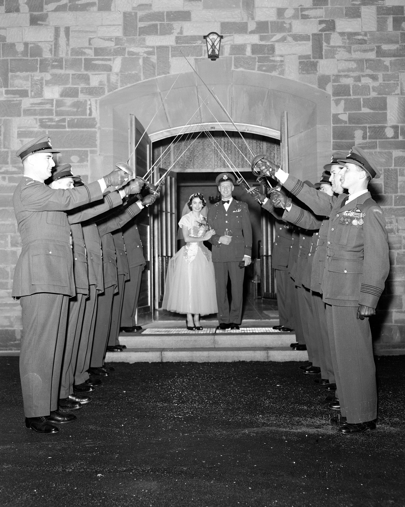 "The original caption of this October 17, 1953 photo reads ""Flight Lieutenant and Mrs. R.A. Anderson coming out of church after their wedding at Zweibrucken, Germany. Flight Lieutenant Anderson, who hails from Kelowna, British Columbia, is the station adjutant. Mrs. Anderson is the former Irene Harris, of Edmonton, Alberta"". PHOTO: DND Archives, PL-58869"