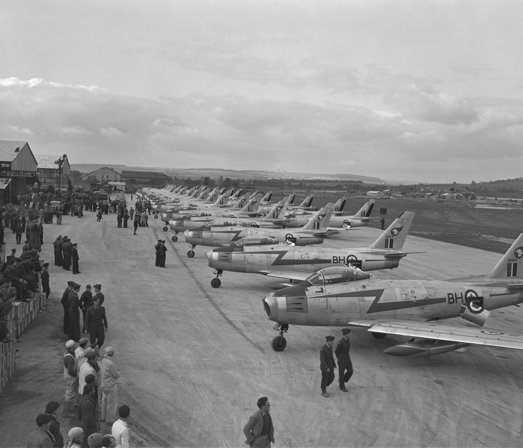 A view of the arrival of No. 2 (Fighter) Wing at Grostenquin, France. Two squadrons have landed and the crowd awaits the arrival of the third. PHOTO: DND Archives, PL-62570