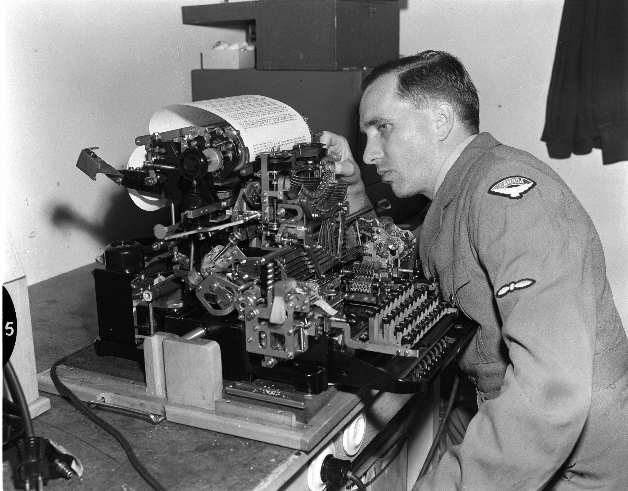 Leading Aircraftman C.G. Ross, a telegraph technician in the Telecommunications Branch at the RCAF's No. 3 (Fighter) Wing in Zweibrucken, Germany, repairs a teletype machine used in transmitting messages from one base to another. PHOTO: DND Archives, PL-81188