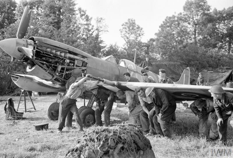 Men of a Royal Air Force Repair and Salvage Unit work on a damaged Supermarine Spitfire Mk IX from 403 Squadron, Royal Canadian Air Force, at a forward airstrip in Normandy on June 19, 1944. PHOTO: Imperial War Museum, CL 186