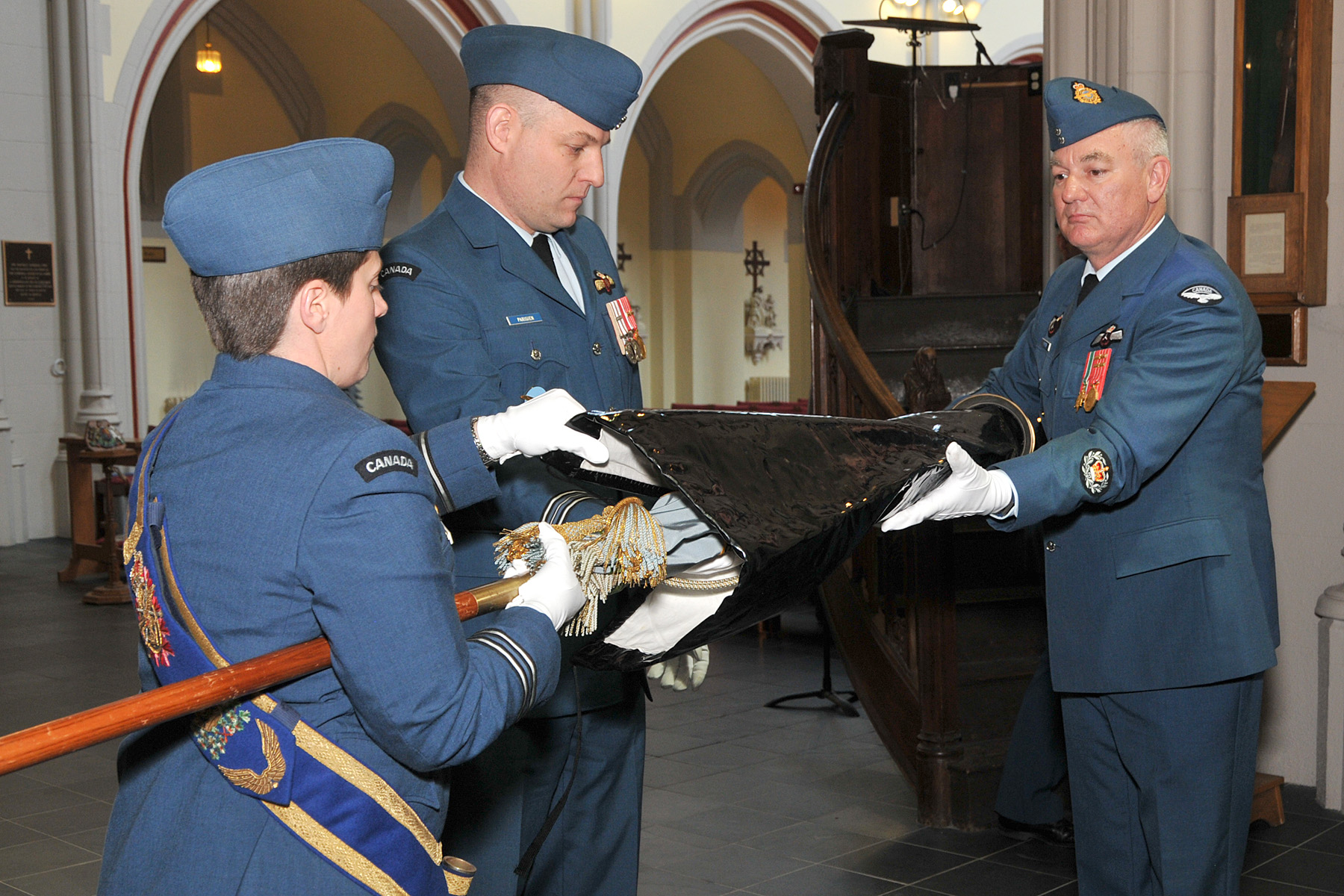 Major Serge Parisien of 434 Operational Test and Evaluation Squadron (centre) assists Captain Julie Perreault (left) and Master Warrant Officer Rene Forster in recasing the 434 Squadron colour to move it from All Saints Cathedral in Halifax, Nova Scotia, to the reborn squadron's headquarters in Trenton, Ontario. PHOTO: Warrant Officer Fran Gaudet, DND Photo