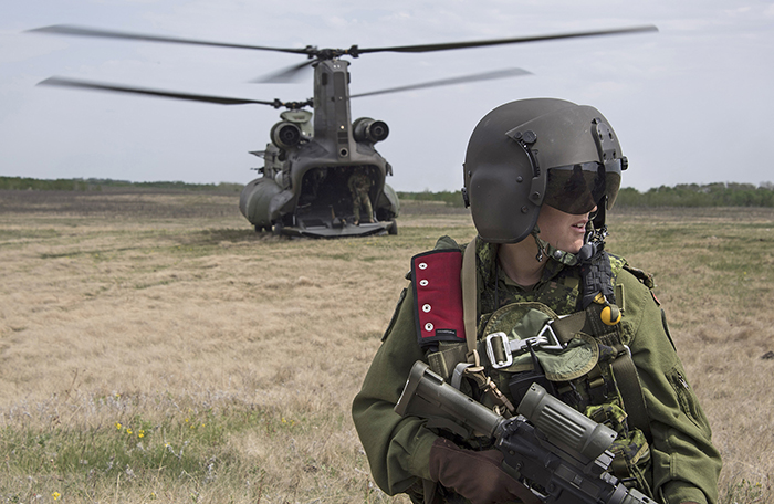 slide - A person wearing a helmet with closed visor and a military uniform holds a rifle. In the background is a large, two-rotored helicopter.