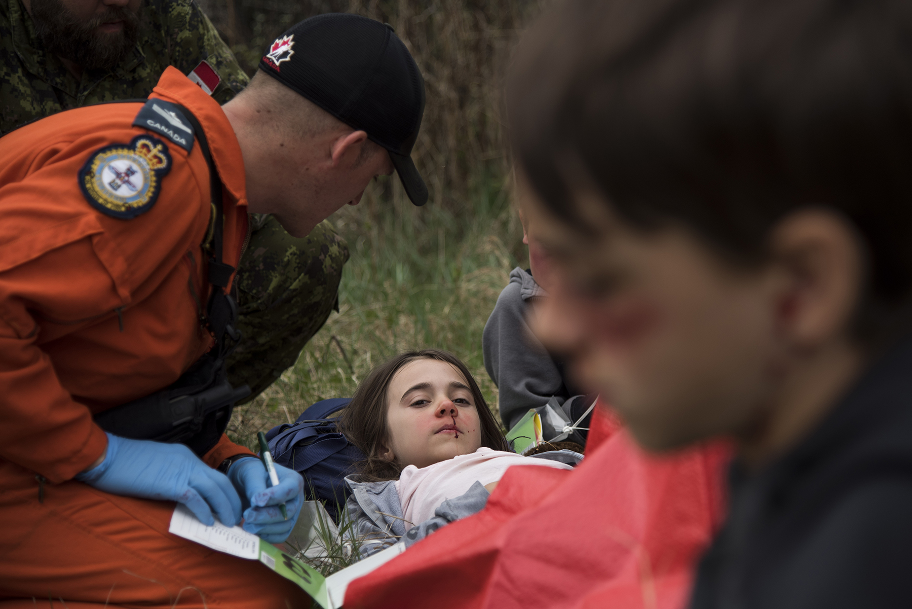 A person wearing orange clothing tends to a girl with simulated injuries.