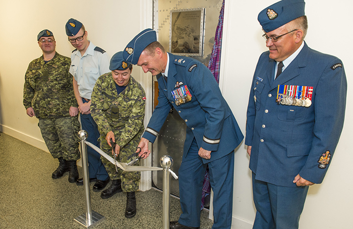 slide - Five people, in various military uniforms stand with a door behind them. Two of them use scissors to cut a ribbon strung between two metal posts in front of them.