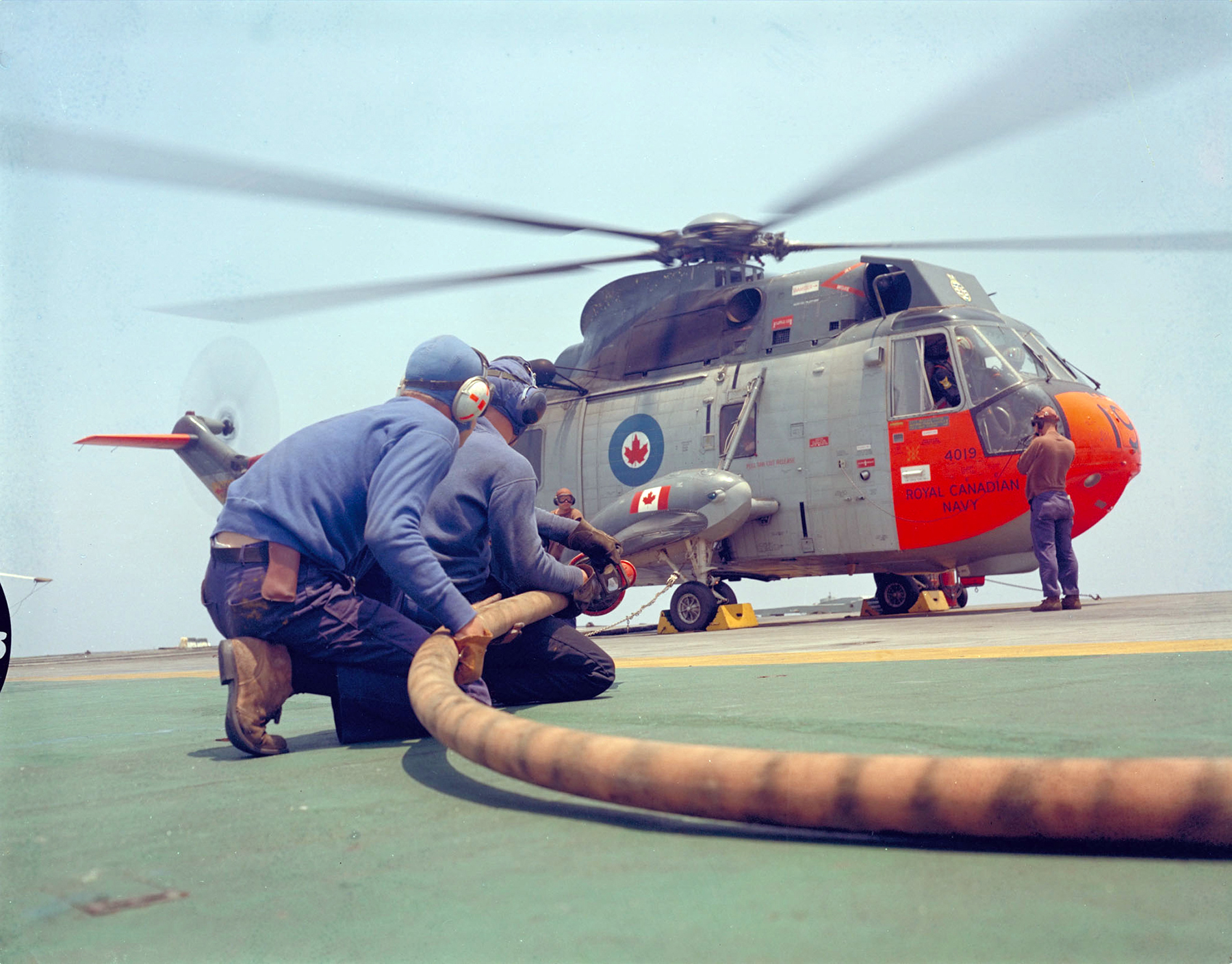 Two air boatswains stand by the fire hose while the ship's CH-124 Sea King helicopter is refueled on the flight deck of Her Majesty's Canadian Ship Bonaventure on June 1, 1968. PHOTO: DND, PCN-68-558