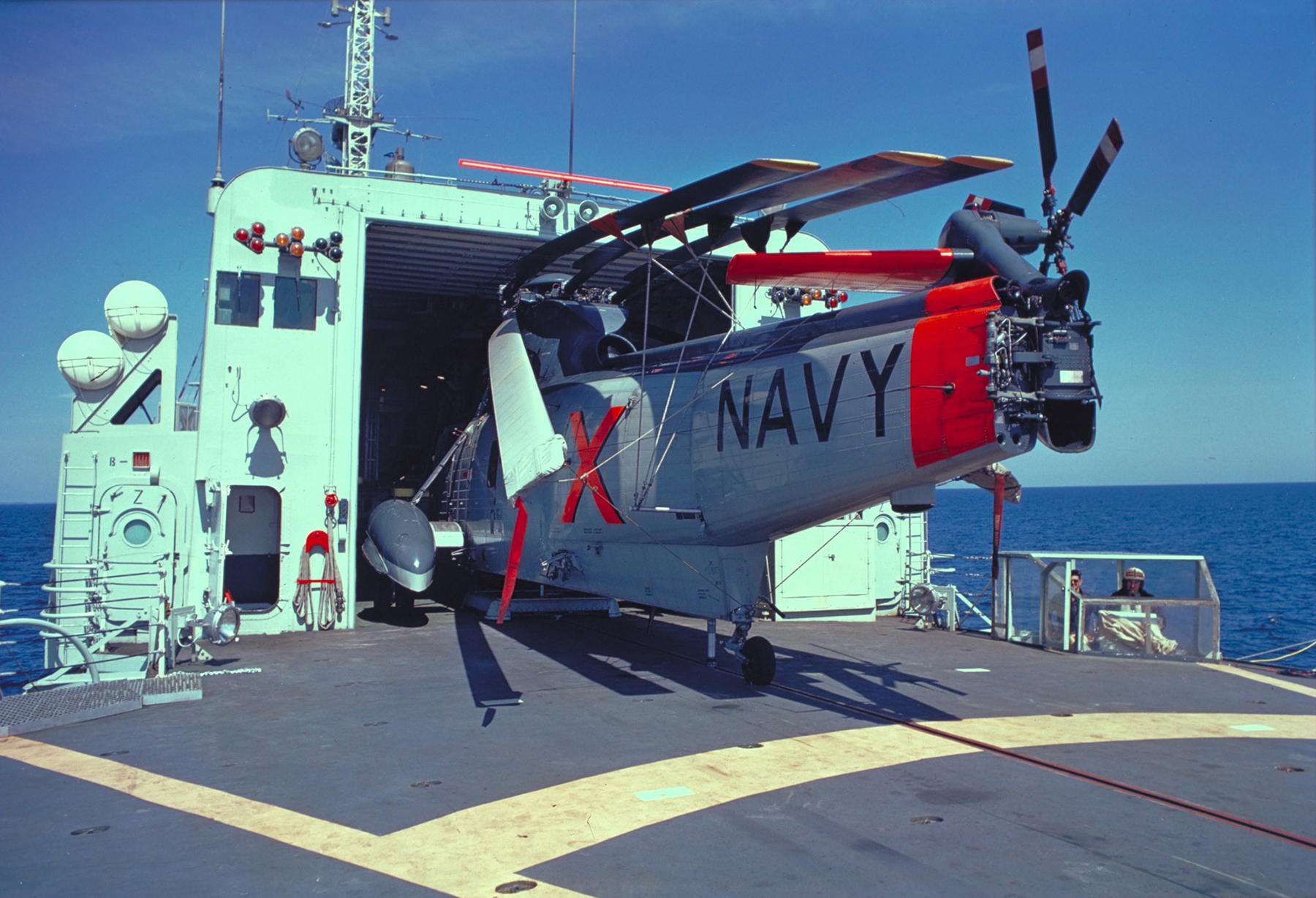 In 1969, a CH-124 Sea King helicopter with its rotor blades folded is moved out of its hangar on the flight deck of a Canadian warship at sea. PHOTO: DND, REC69-102