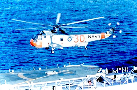 In a vintage colour photograph, a Canadian Navy Sea King helicopter hovers above the flight deck of a ship at sea. PHOTO: DND