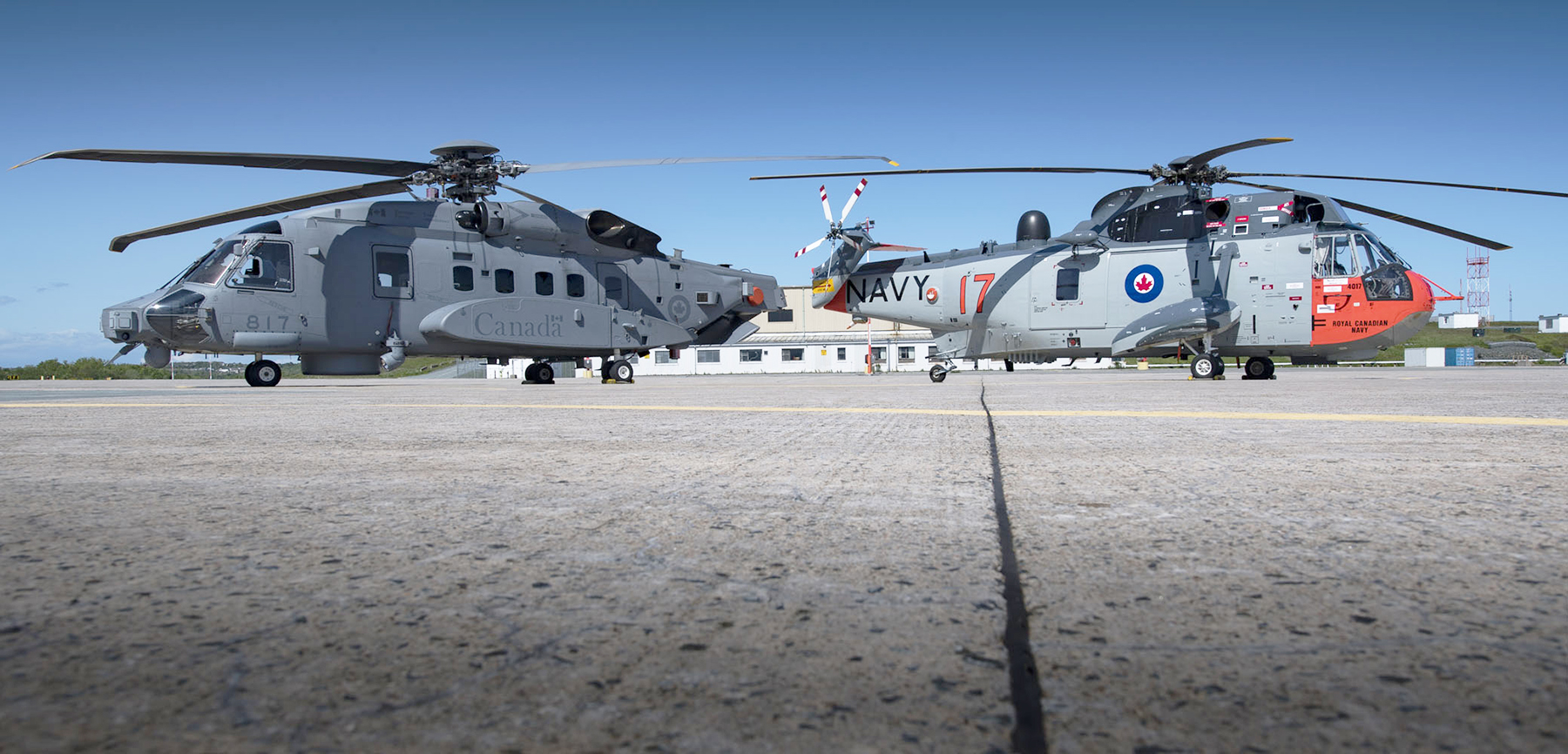 The Sea King helicopter CH12417, which has been painted in its original Royal Canadian Navy livery in honour of the venerable helicopter's upcoming retirement (right), and a CH-148 Cyclone helicopter sit on the tarmac at 12 Wing Shearwater, Nova Scotia, on June 7, 2018. PHOTO: Leading Seaman Laurance Clarke, SW05-2018-0245-002