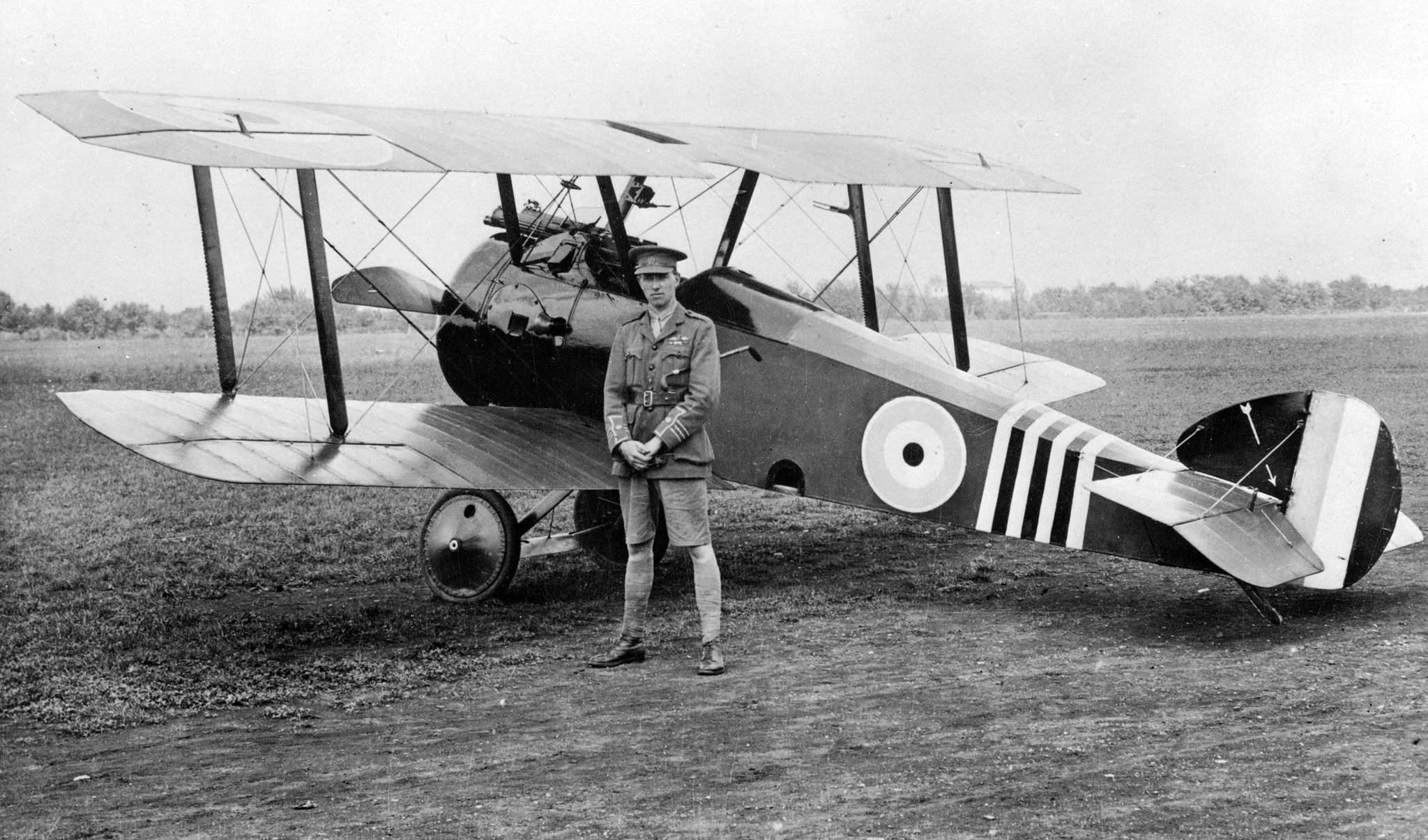 An old black and white photograph of a man in military uniform standing in front of a bi-plane.