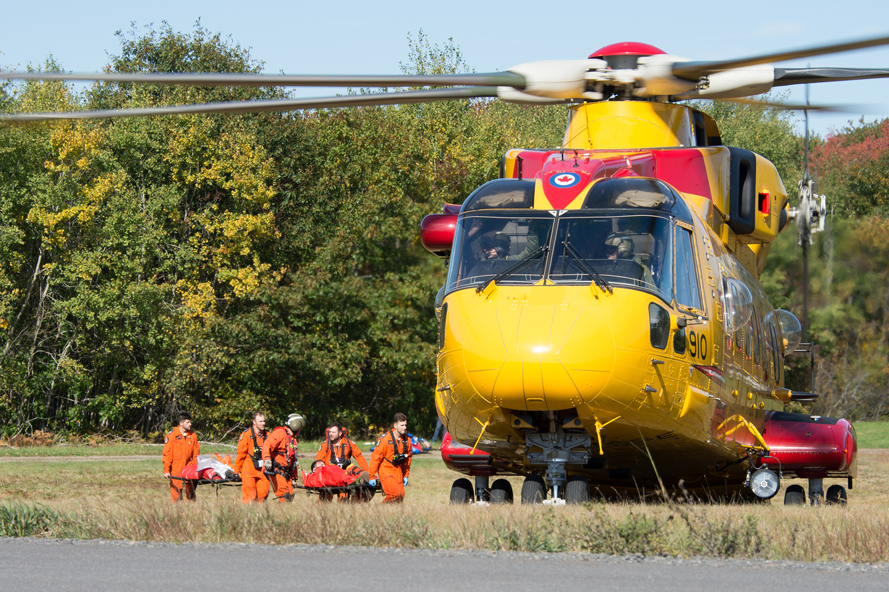 Search and rescue technicians load simulated casualties onto a CH-149 Cormorant helicopter at a simulated crash site at 14 Wing Greenwood during 413 Transport and Rescue Squadron's search and rescue exercise on October 5, 2018. PHOTO: Corporal Karen Neate, GD10-2018-0688-171