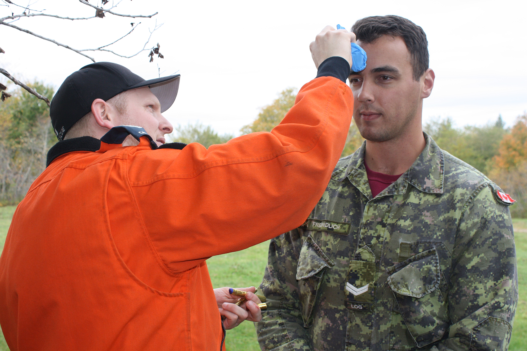 Search and rescue technician Master Corporal Alexandre Lanoix puts the final touches on volunteer victim Corporal Philip Freundlich's simulated head injury for a two-aircraft crash scenario as 413 Transport and Rescue Squadron's search and rescue exercise  gets underway. PHOTO: Sara White